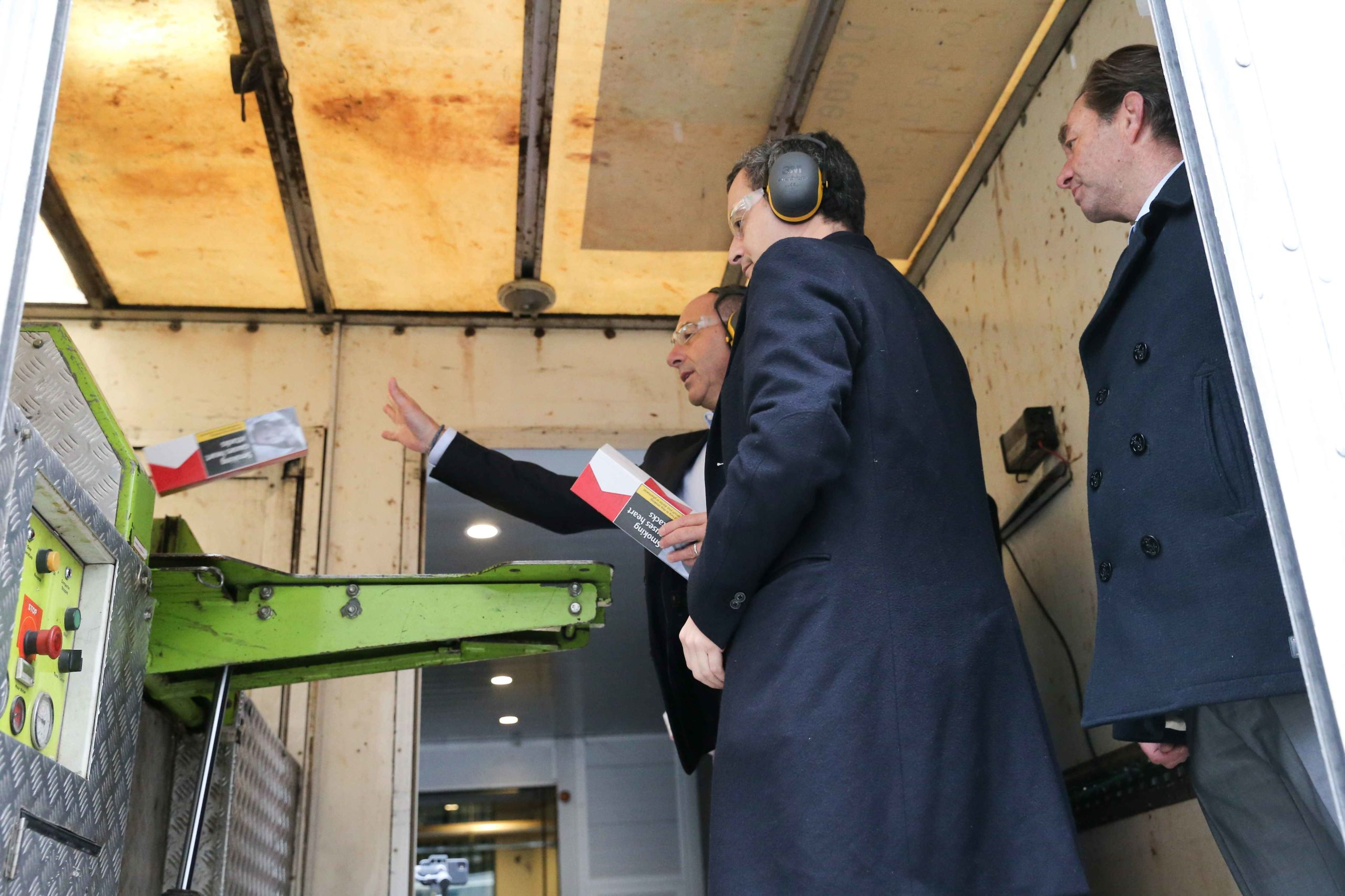 French Minister of Public Action and Accounts Gerald Darmanin (C) destroys illegal cigarettes in a shredder at the Paris regional customs service on February 04, 2020, where he went to present the 2019 results of the National plan to mobilise customs again
