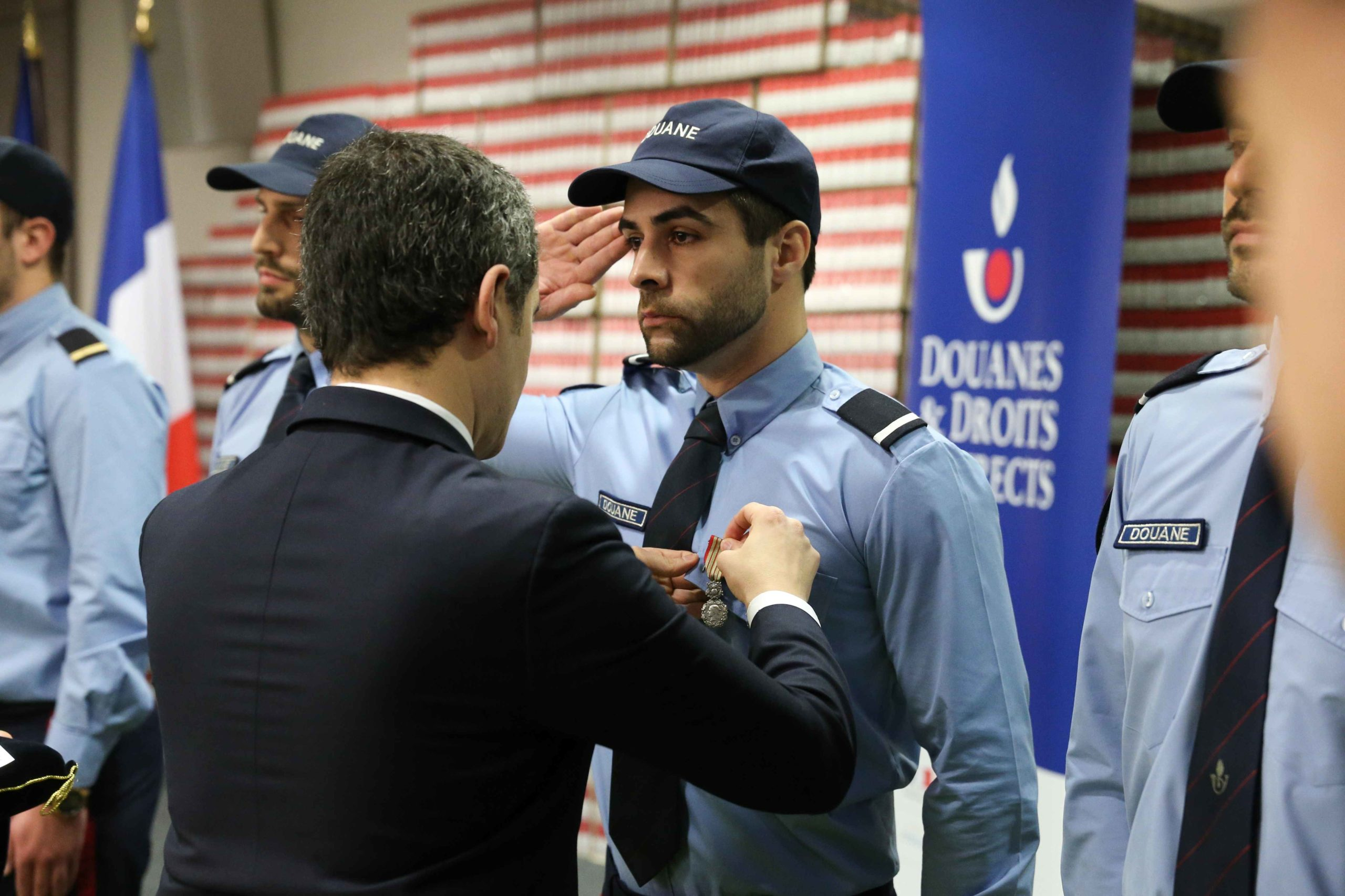 French Minister of Public Action and Accounts Gerald Darmanin (C) pins a medal to a customs officer in the Paris regional customs service on February 04, 2020, where he went to present the 2019 results of the National plan to mobilise customs against the t