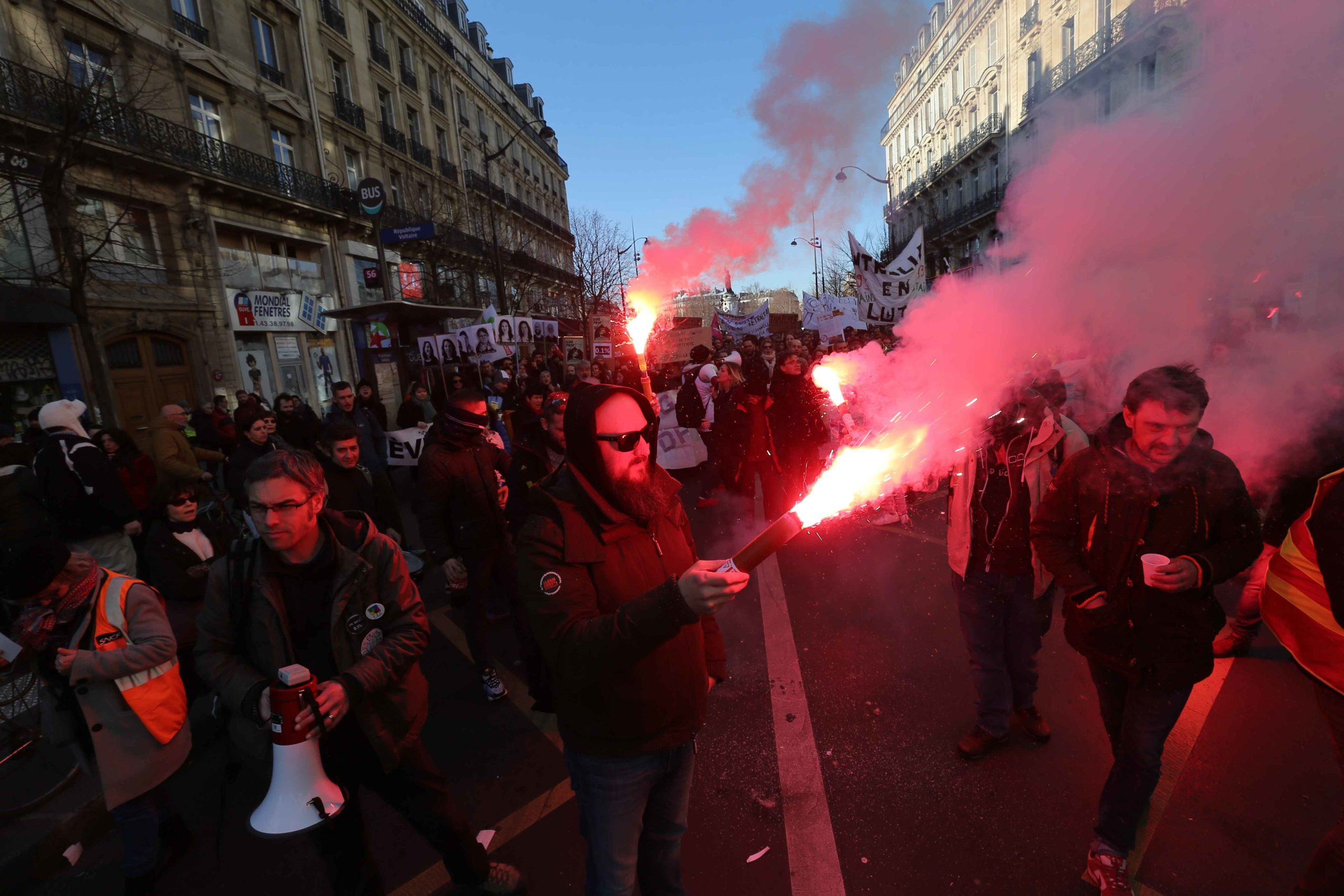 Protesters hold burning flares during a demonstration against the French government's plan to overhaul the country's retirement system in Paris, on February 6, 2020. Protesters took to the streets in a ninth inter-professional day of strikes and demonstrat