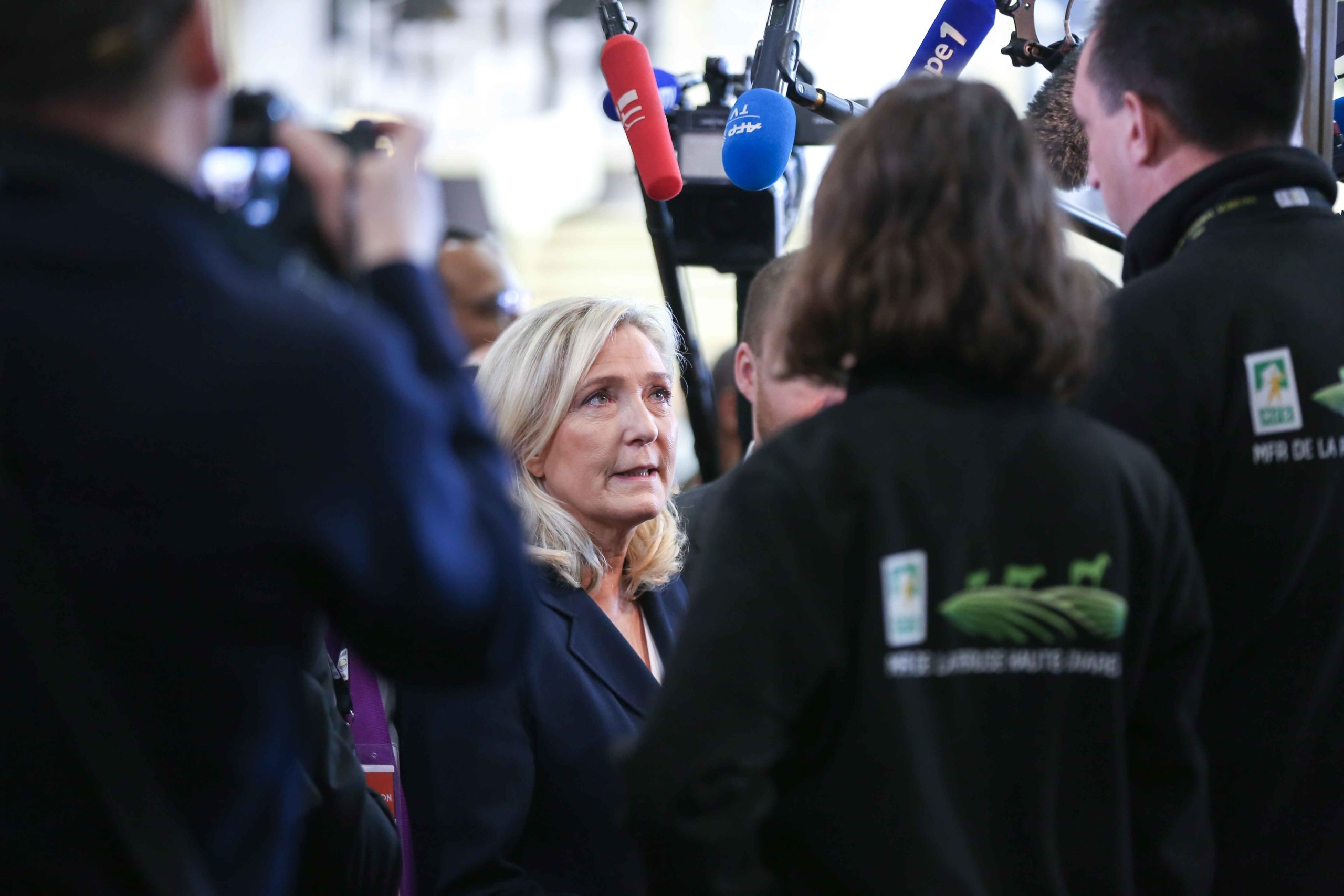 French member of Parliament and President of the far-right Rassemblement National (RN) party Marine Le Pen (C) visits the international Agriculture Fair in Paris on February 25, 2020.