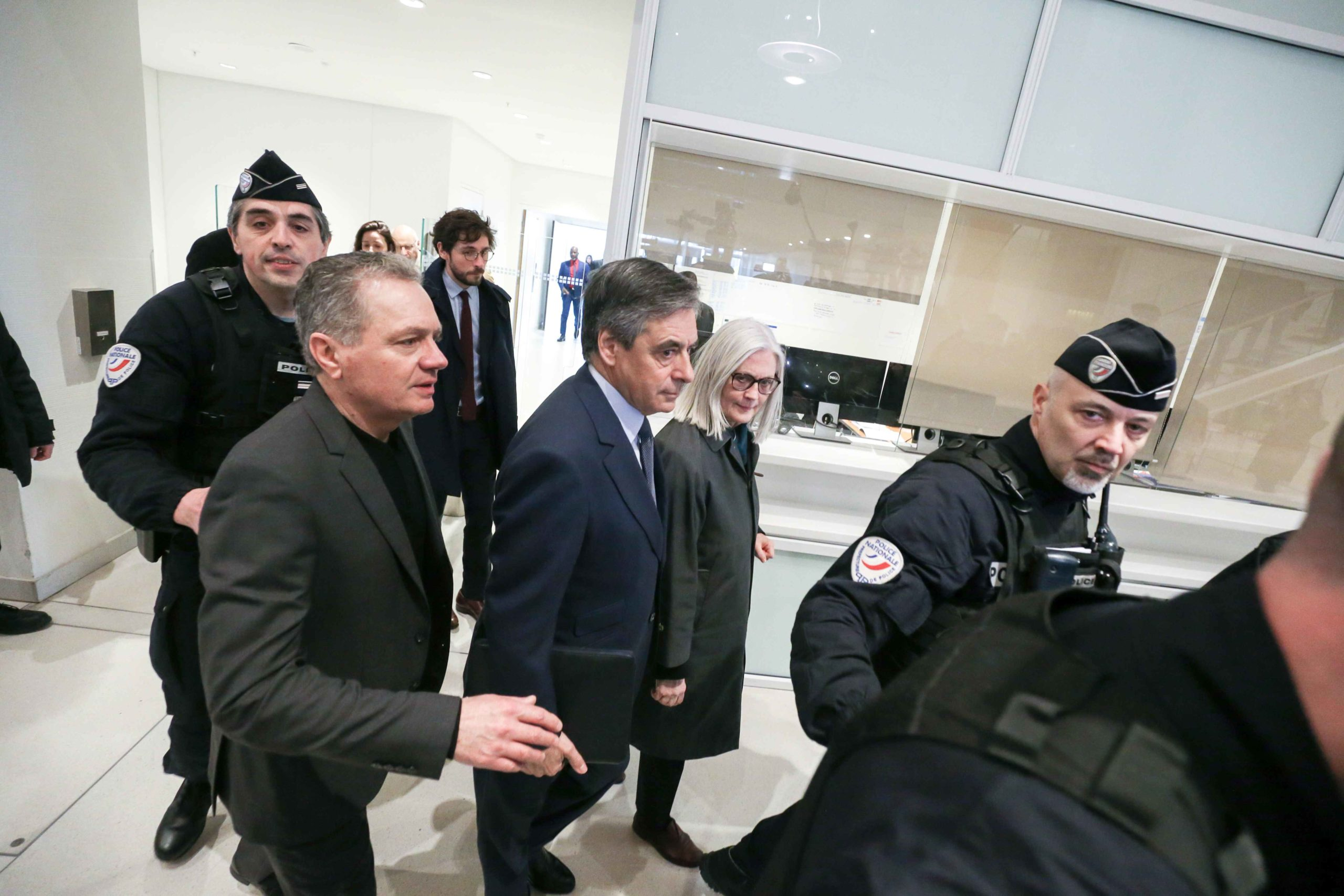 Former French Prime minister Francois Fillon (C-L) and his wife Penelope (C-R) arrive at Paris' courthouse, on February 26, 2020, for the opening hearing of their trial over claims they embezzled over one million euros in an alleged fake-jobs fraud. Invest
