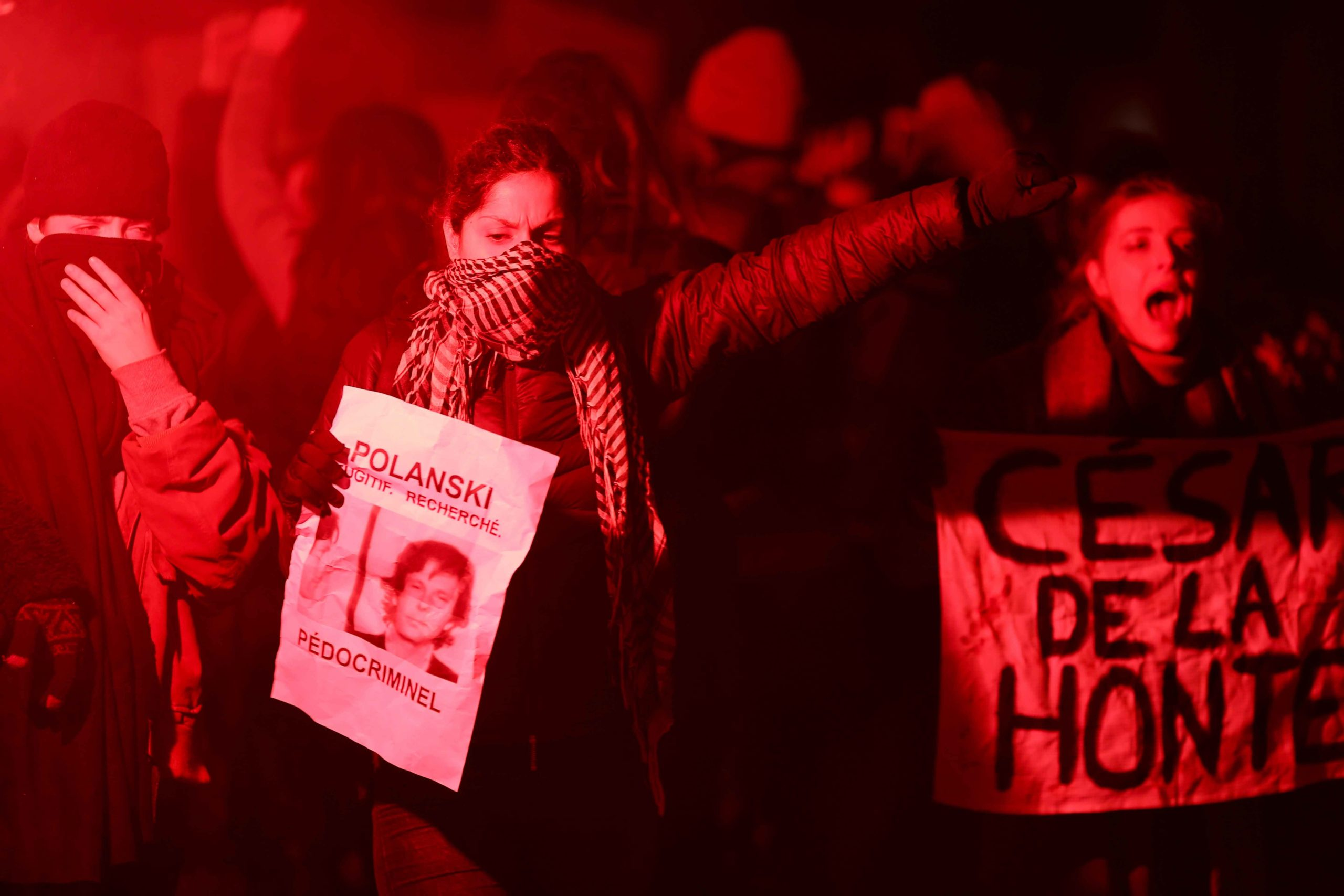 Feminist activists holding signs and red flares demonstrate outside the Salle Pleyel in Paris as guests arrive for the 45th edition of the Cesar Film Awards ceremony on February 28, 2020. The academy organising France's Cesar awards is going through a cris