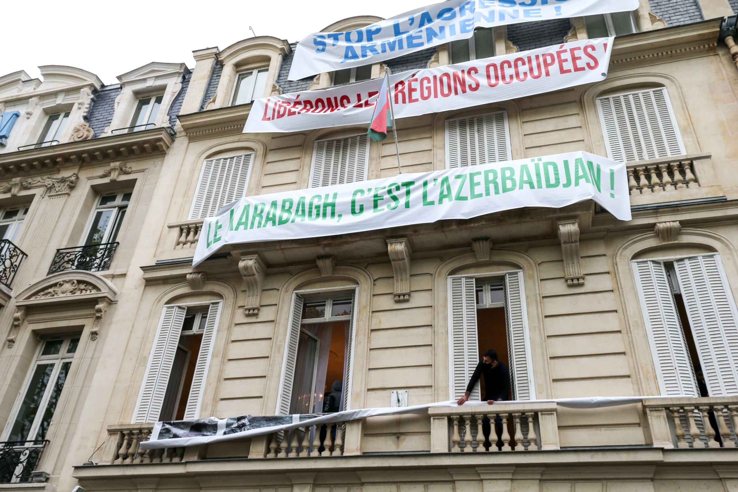 "Banners are hung by the staff of the Azerbaijani embassy in Paris on the facade of the building, reading ""Stop the Armenian aggression"", ""Free the occupied regions"", ""Karabakh is Azerbaijan"", during a demonstration of Armenians in front of the ambassy,"