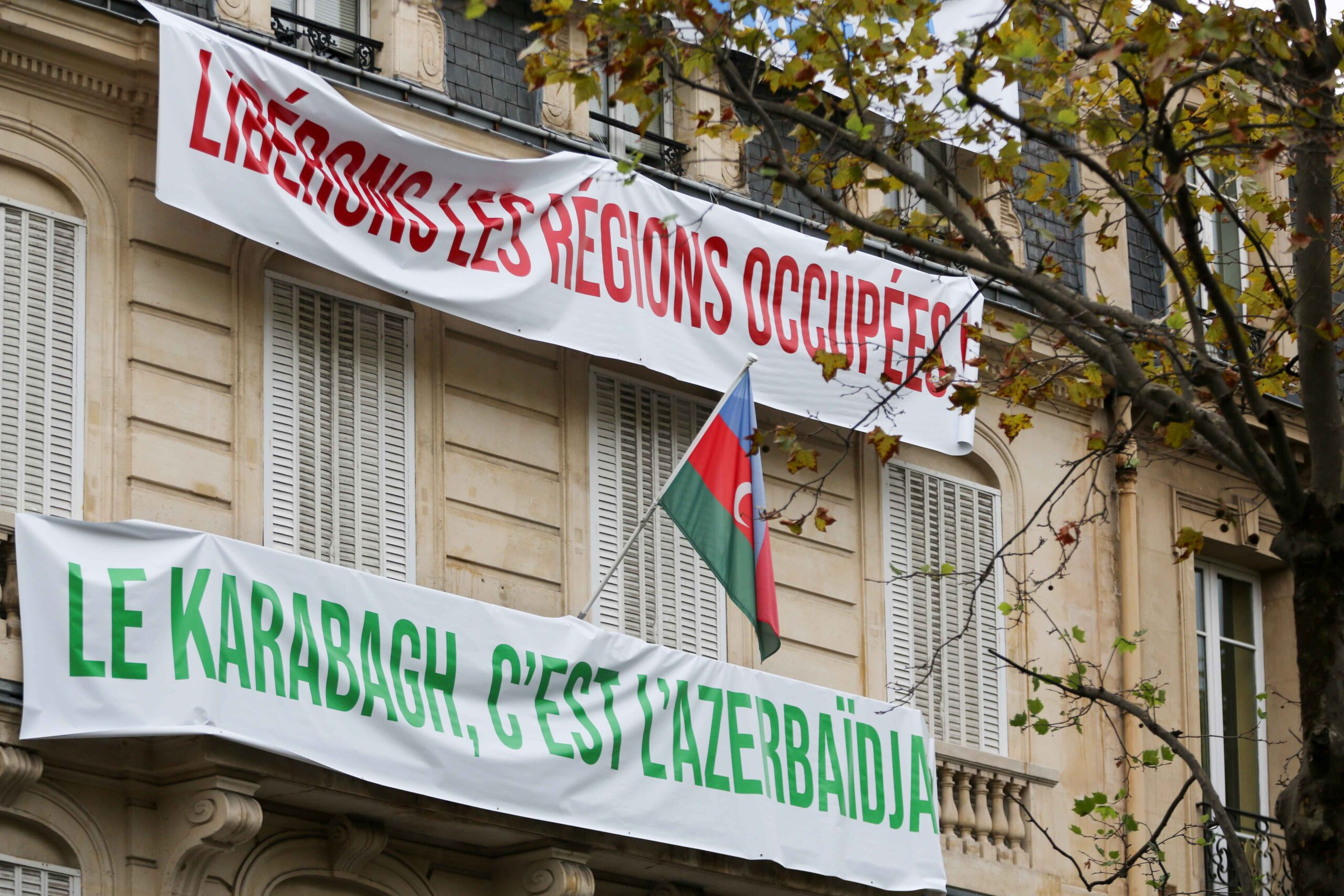 """Banners are hung by the staff of the Azerbaijani embassy in Paris on the facade of the building, reading """"Free the occupied regions"""", """"Karabakh is Azerbaijan"""", during a demonstration of Armenians in front of the ambassy, on September 29, 2020 against t"""