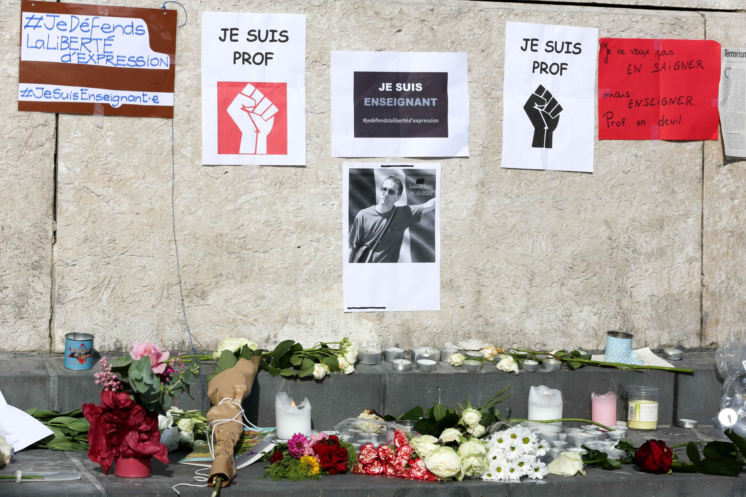 Flowers are placed in front of the portrait of history teacher Samuel Paty as people gather on Place de la Republique in Paris on October 18, 2020, two days after he was beheaded by an attacker who was shot dead by policemen. Thousands of people rally in P