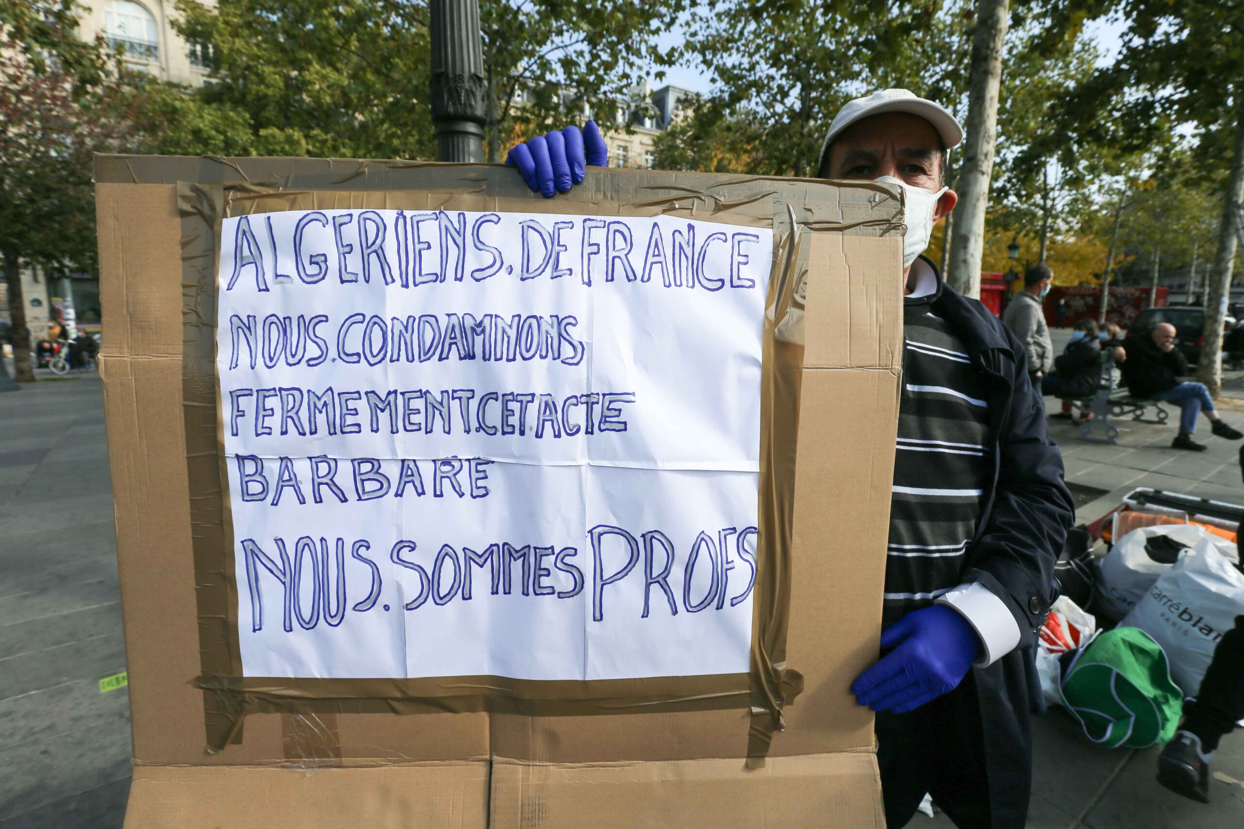 A man holds a placard reading « France's Algerians but we strongly condemn this barbaric act. We are teachers » as people gather on Place de la Republique in Paris on October 18, 2020, in homage to history teacher Samuel Paty two days after he was behe