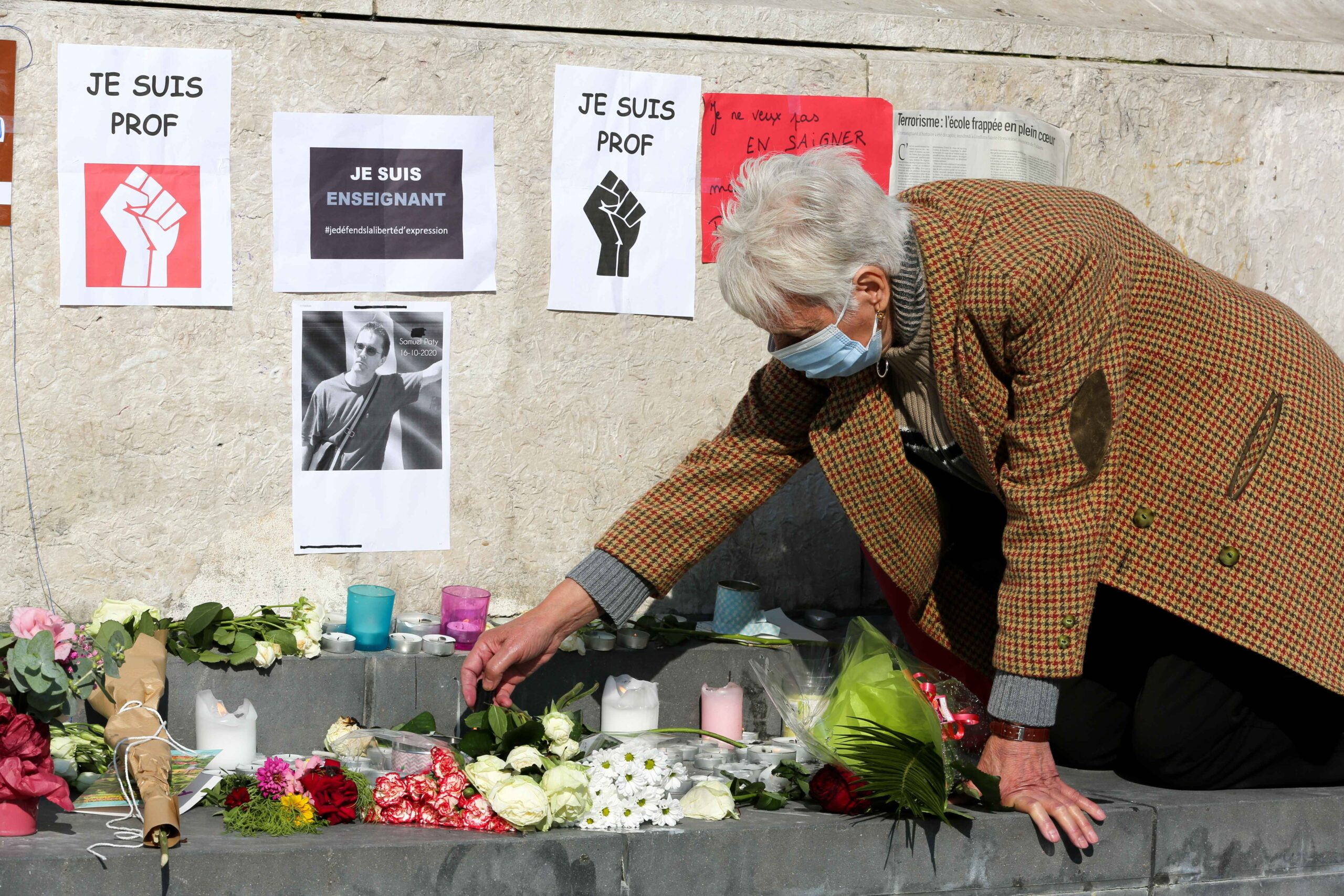 A person places flowers in front of the portrait of history teacher Samuel Paty as people gather on Place de la Republique in Paris on October 18, 2020, two days after he was beheaded by an attacker who was shot dead by policemen. Thousands of people rally