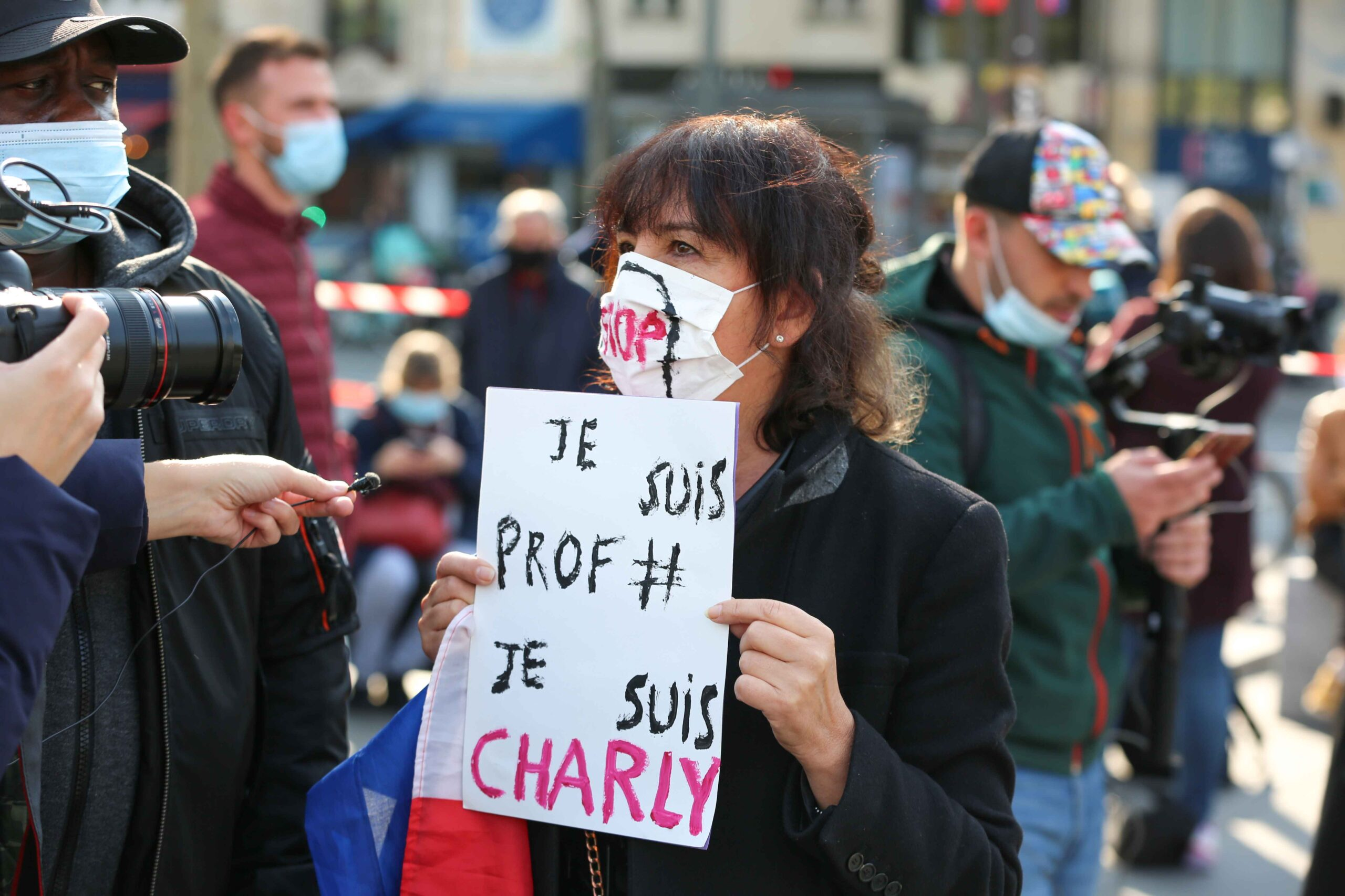 A  woman holds a placard reading « I'm a teacher, I'm Charlie » as people gather on Place de la Republique in Paris on October 18, 2020, in homage to history teacher Samuel Paty two days after he was beheaded by an attacker who was shot dead by polic