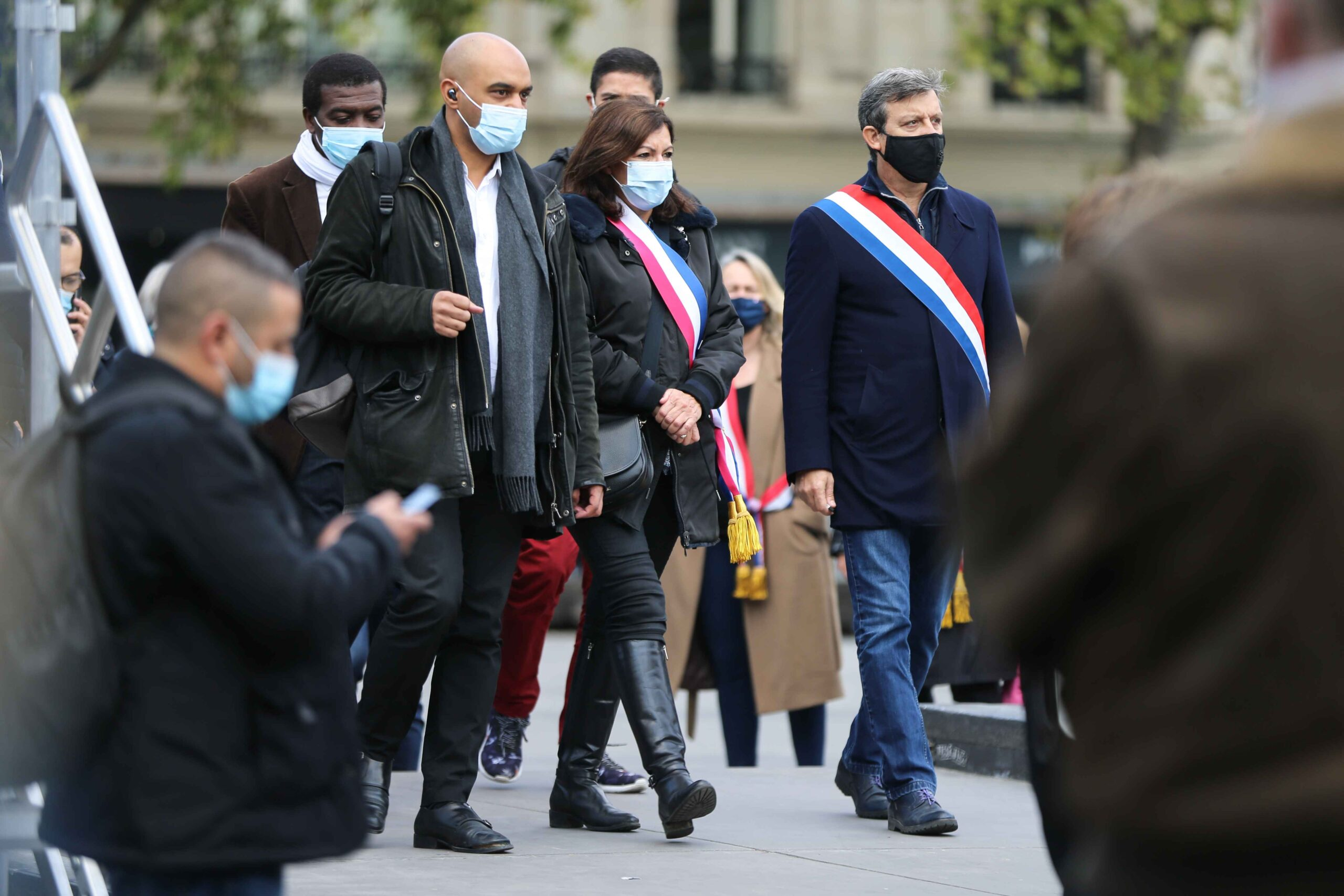 Mayor of Paris Anne Hidalgo (3R) and Head of SOS Racisme anti-racist NGO Dominique Sopo (4R) arrive as people gather on Place de la Republique in Paris on October 18, 2020, in homage to history teacher Samuel Paty two days after he was beheaded by an attac