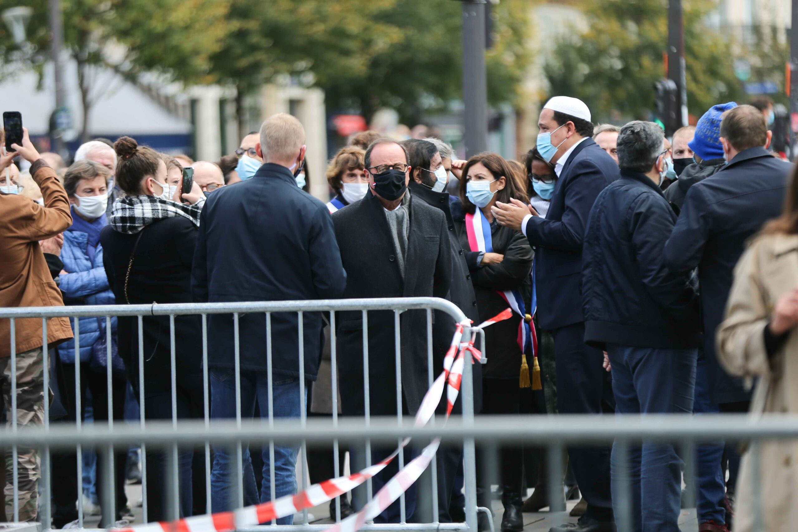 Former French President Francois Hollande (C) stands as people gather on Place de la Republique in Paris on October 18, 2020, in homage to history teacher Samuel Paty two days after he was beheaded by an attacker who was shot dead by policemen. Thousands o