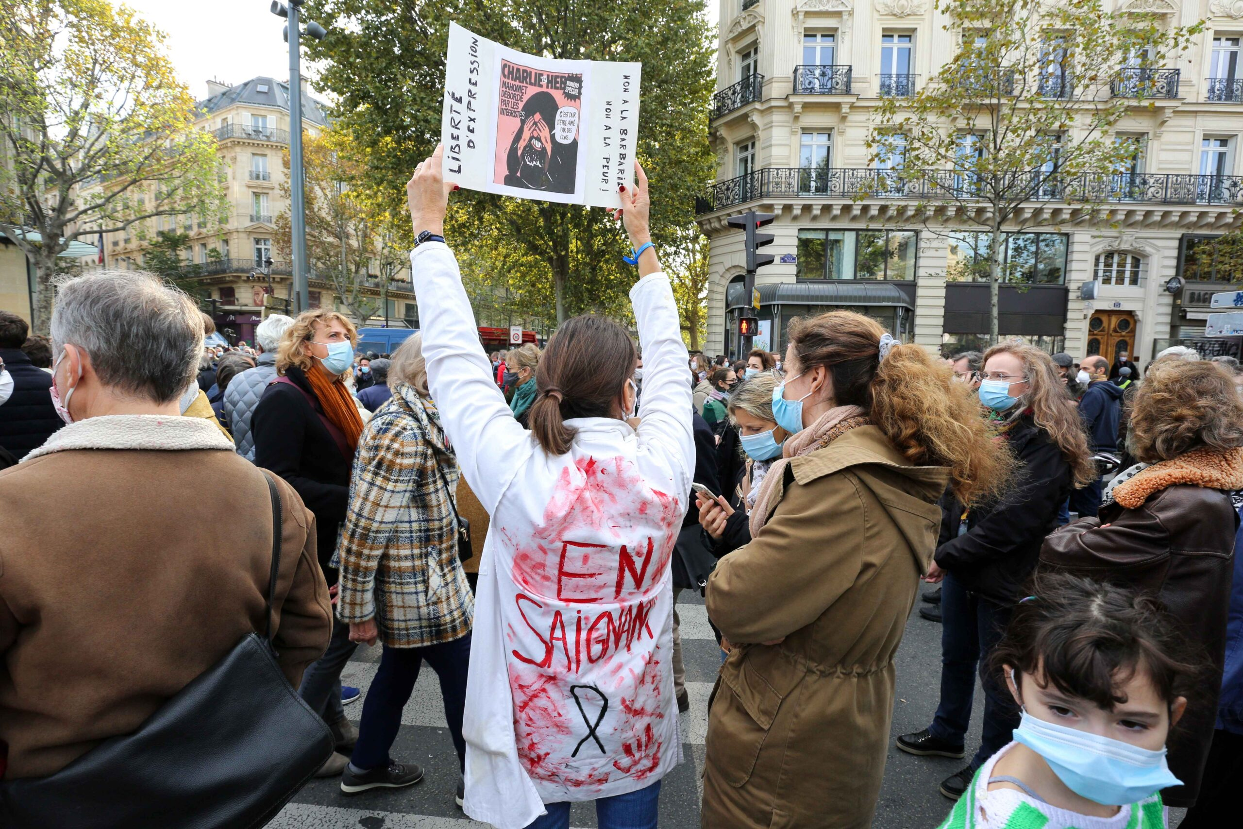 A woman wearing a blood-stained blouse holds a copy of the satirical newspaper Charlie Hebdoas people gather on Place de la Republique in Paris on October 18, 2020, two days after he was beheaded by an attacker who was shot dead by policemen. Thousands of