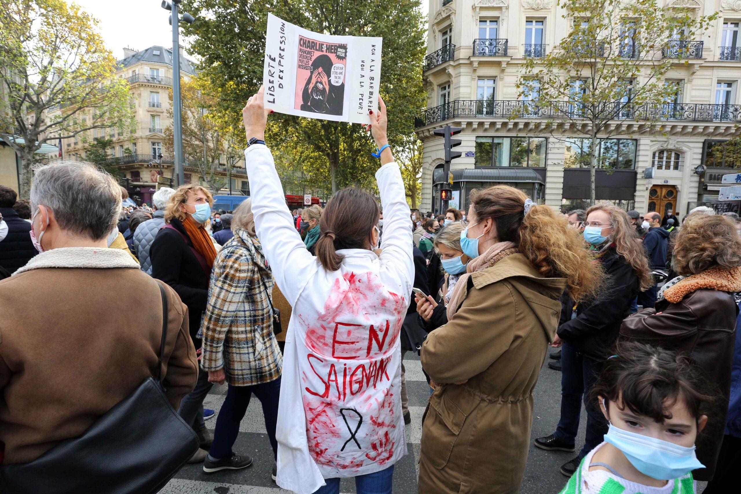 Une femme vêtue d'une blouse ensanglantée tient une copie de Chalie-Hebdo. © Michel Stoupak. Dim 18.10.2020, 14h46m31.
