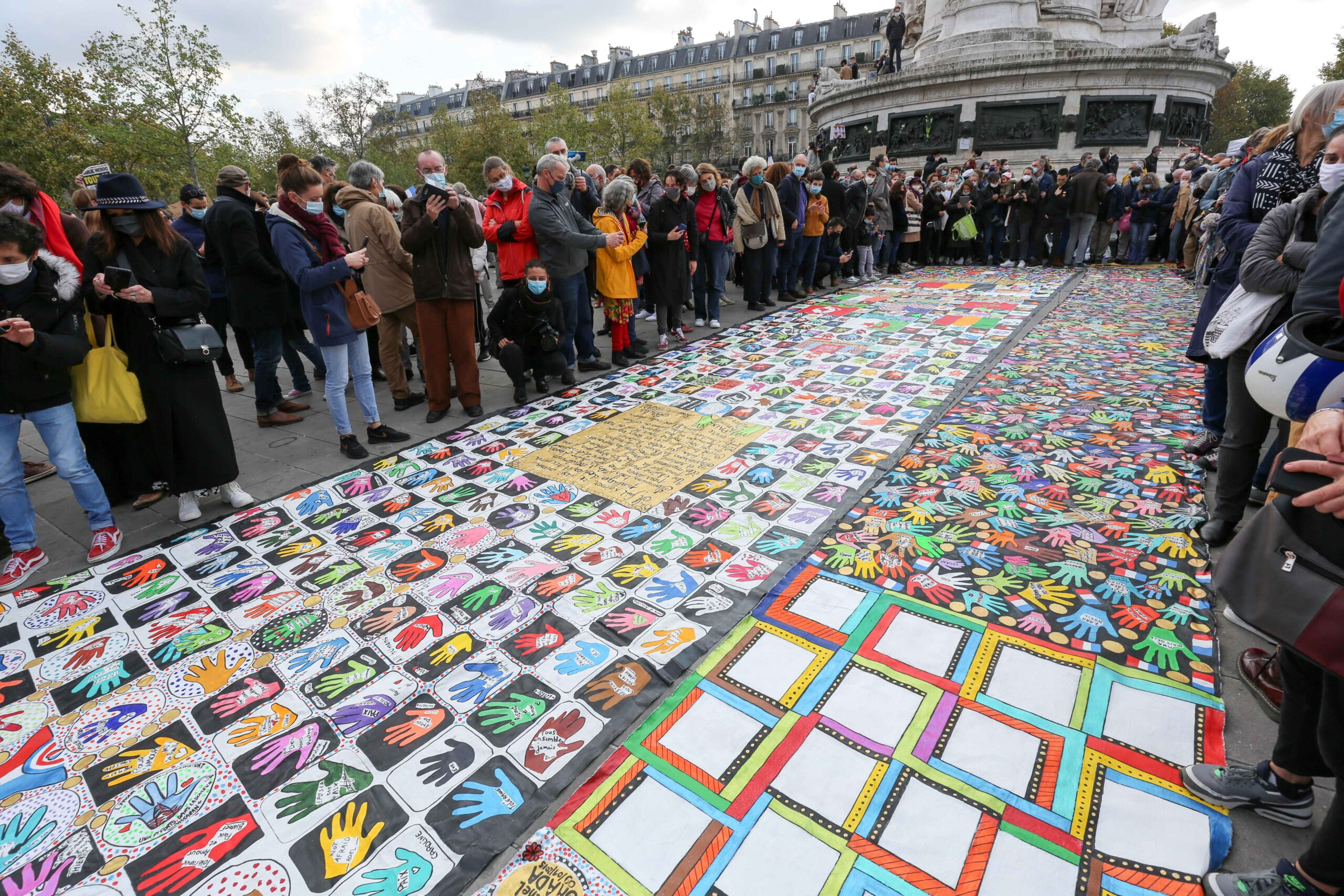 People gather on Place de la Republique in Paris on October 18, 2020, in homage to history teacher Samuel Paty two days after he was beheaded by an attacker who was shot dead by policemen. Thousands of people rally in Paris and other French cities on Octob