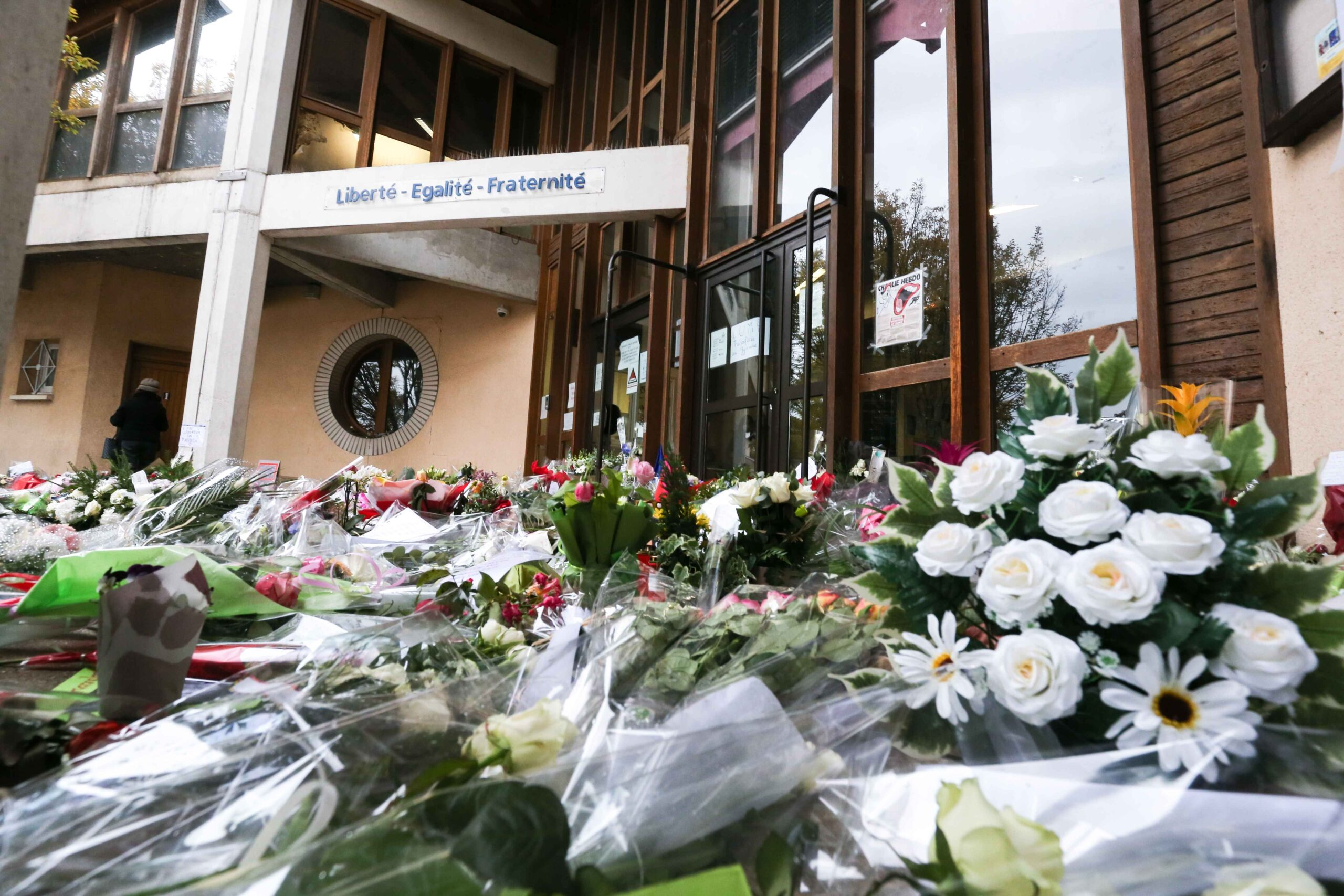 Flowers are placed outside the Bois d'Aulne secondary school in homage to slain history teacher Samuel Paty, who was beheaded by an attacker for showing pupils cartoons of the Prophet Mohammed in his civics class, on October 19, 2020, in Conflans-Sainte-Ho