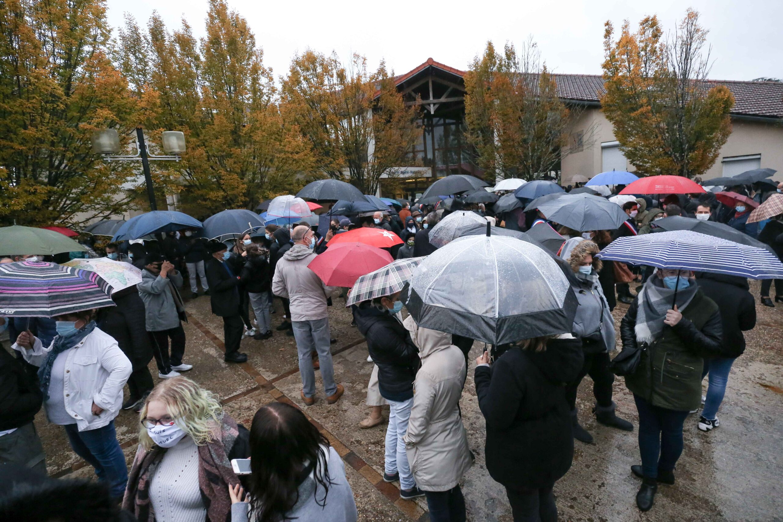 People gather at the middle school in Conflans-Sainte-Honorine, northwest of Paris, on October 20, 2020 during the 'Marche Blanche' in solidarity after a teacher was beheaded for showing pupils cartoons of the Prophet Mohammed. His murder in a Paris suburb