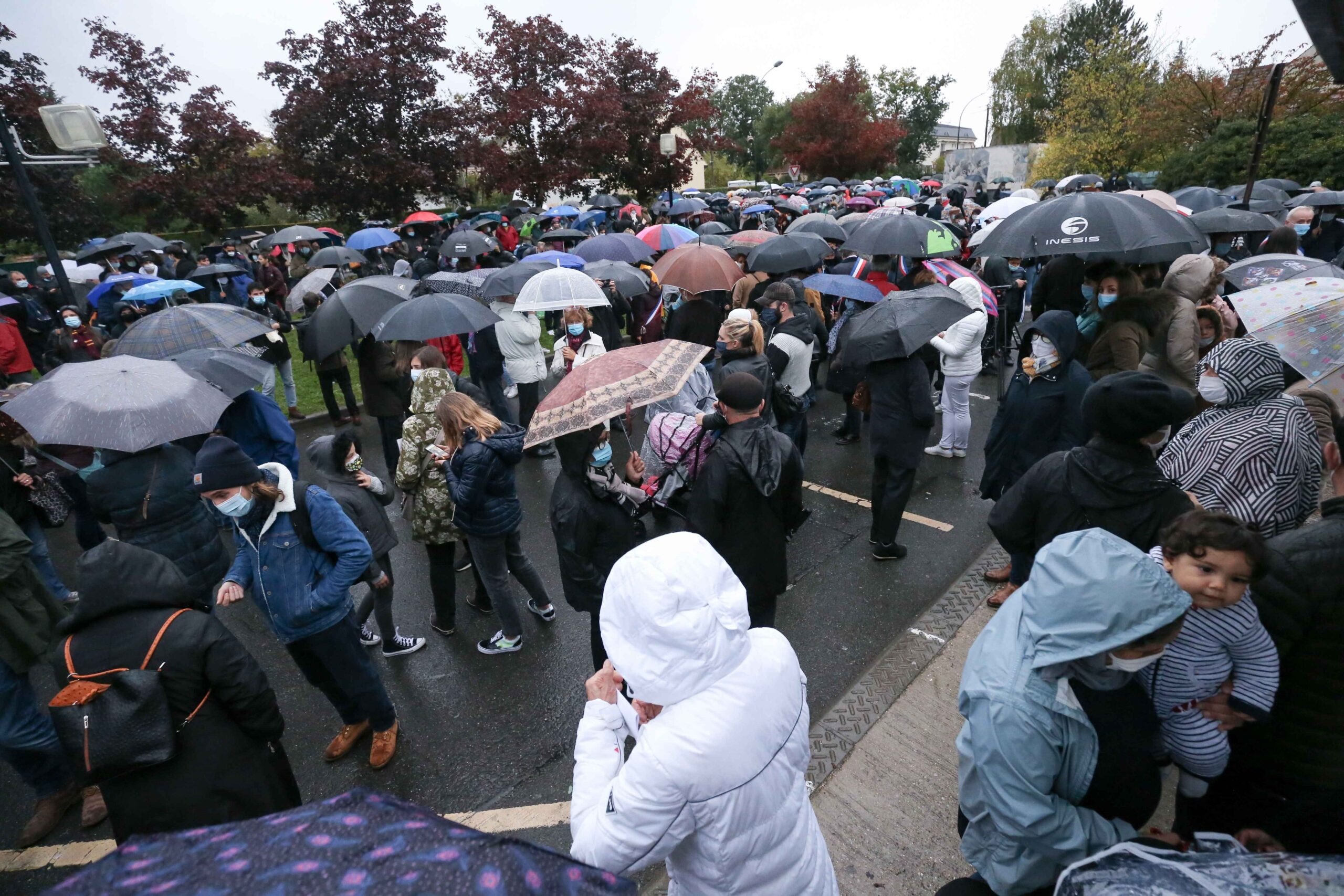 People attend the 'Marche Blanche' in Conflans-Sainte-Honorine, northwest of Paris, on October 20, 2020, in solidarity after a teacher was beheaded for showing pupils cartoons of the Prophet Mohammed. His murder in a Paris suburb on October 16 shocked the