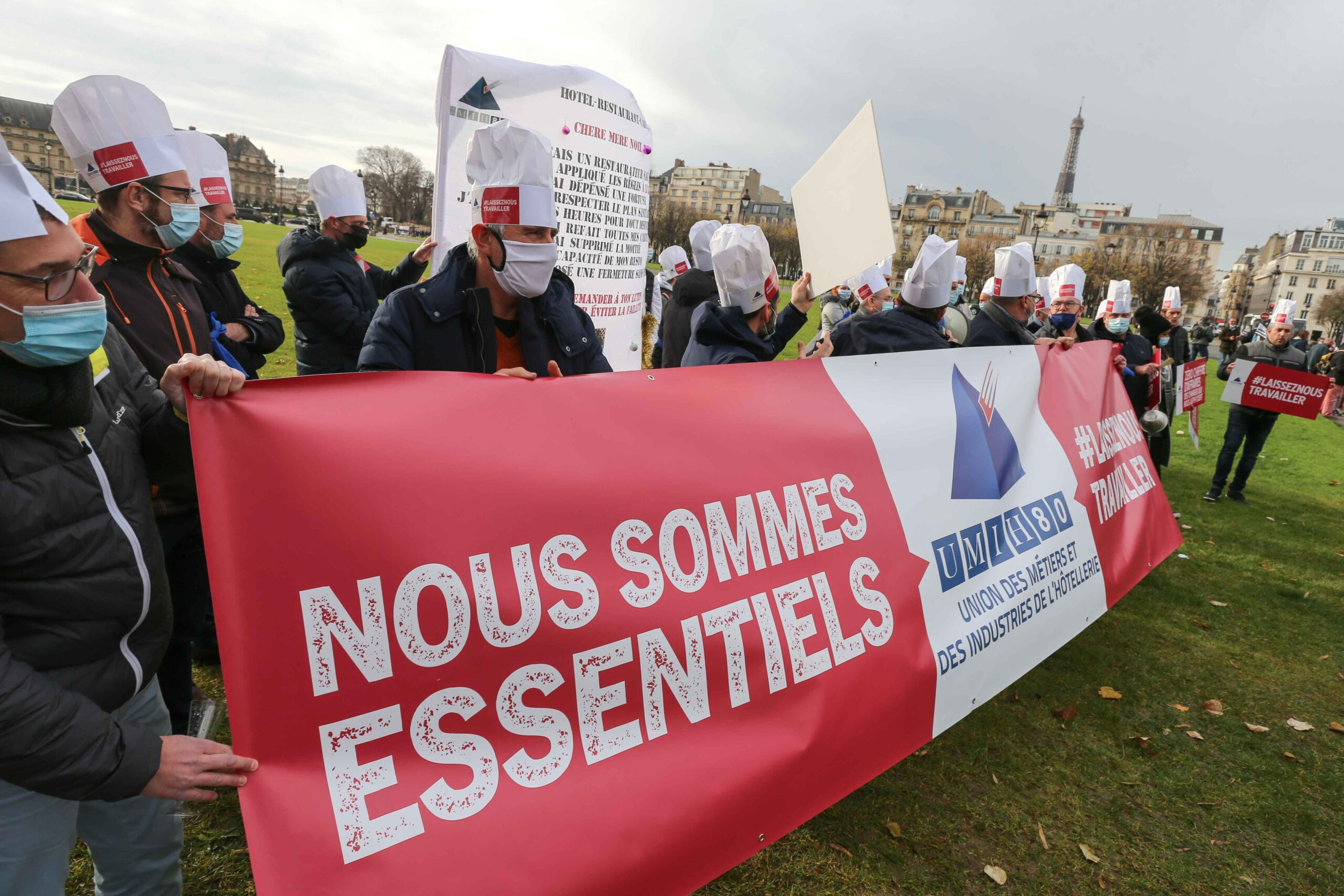 "Protesters hold a banner reading ""we are essential » on December 14, 2020 in Paris during a demonstration of hotel and restaurant owners as well as tourism professionals to demand their businesses to reopen amidst the Covid-19 pandemic, caused by the nove"