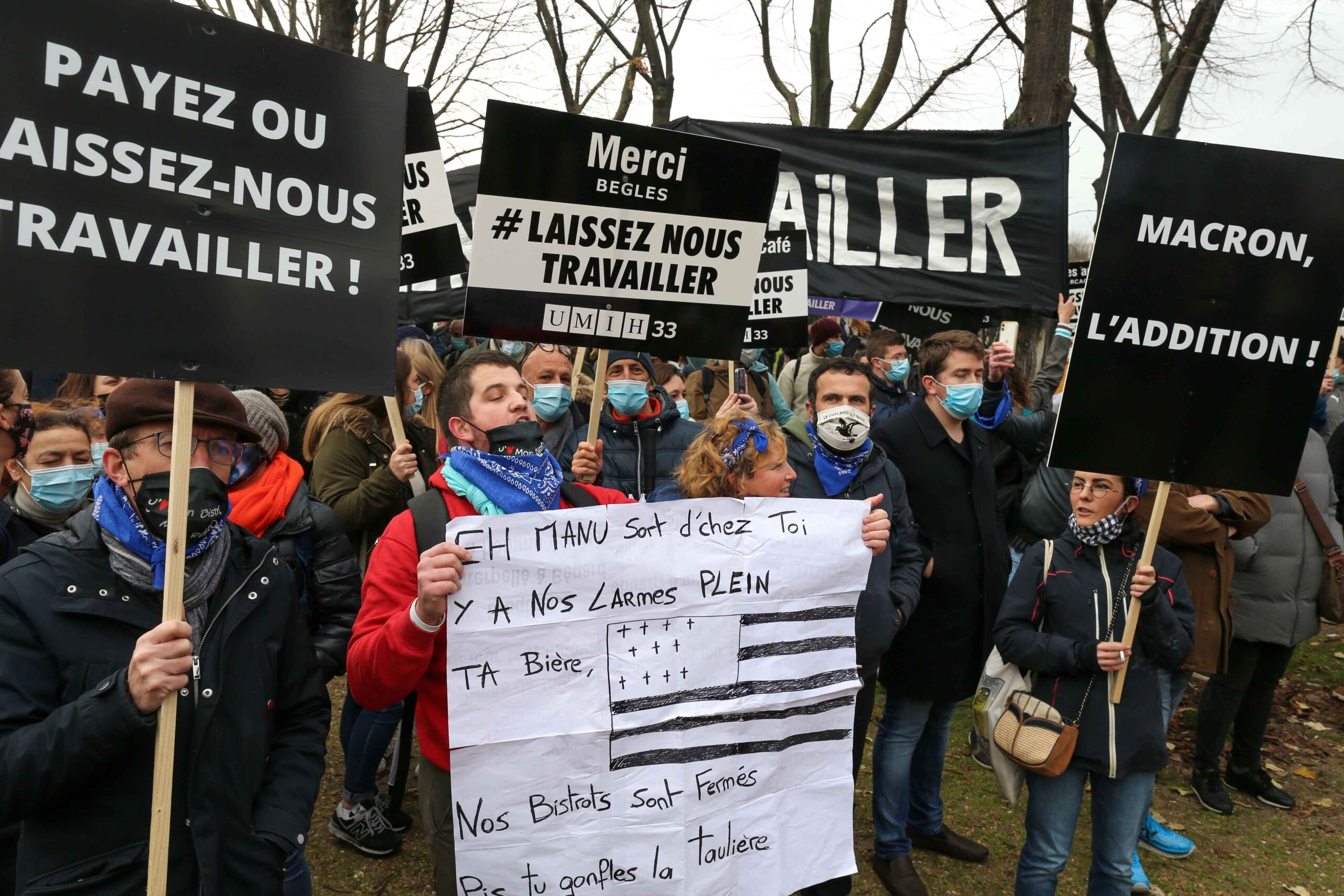 "Protesters hold placards and banners reading ""let us work"" on December 14, 2020 in Paris during a demonstration of hotel and restaurant owners as well as tourism professionals to demand their businesses to reopen amidst the Covid-19 pandemic, caused by the"