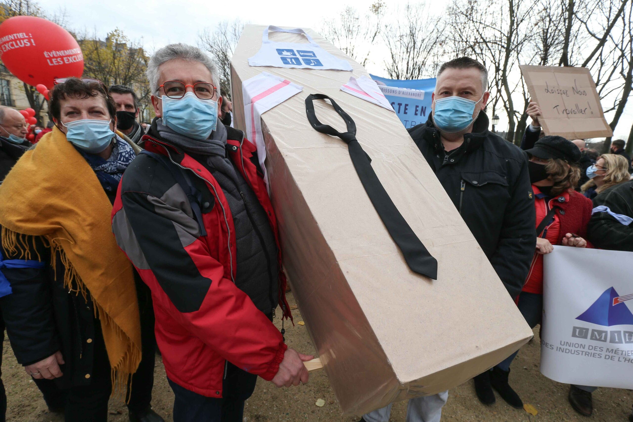 Protesters hold a mock coffin on December 14, 2020 in Paris during a demonstration of hotel and restaurant owners as well as tourism professionals to demand their businesses to reopen amidst the Covid-19 pandemic, caused by the novel coronavirus. The placa