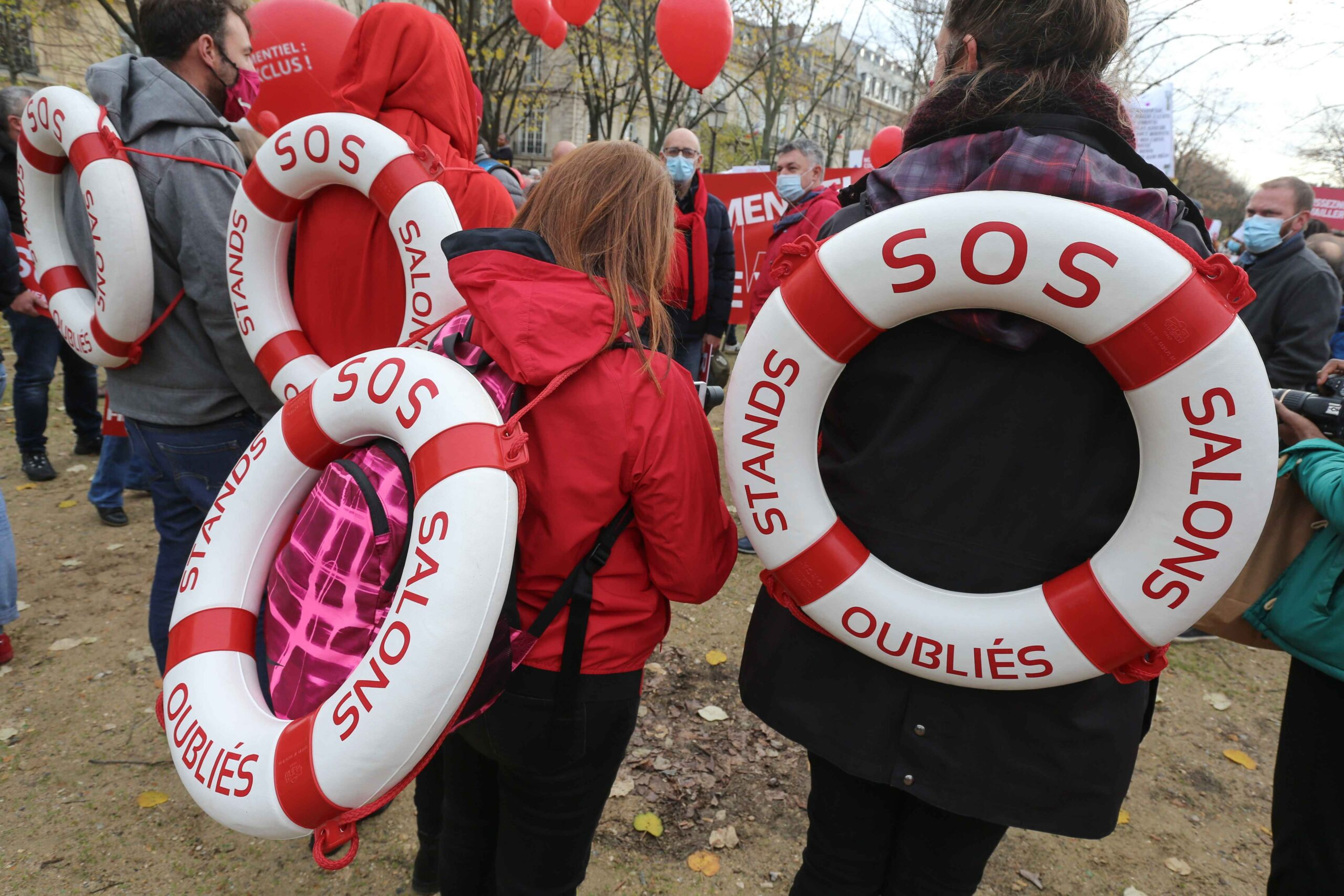 Protesters hold lifebuoys  reading « SOS fair expo stand » on December 14, 2020 in Paris during a demonstration of hotel and restaurant owners as well as tourism professionals to demand their businesses to reopen amidst the Covid-19 pandemic, caused by t