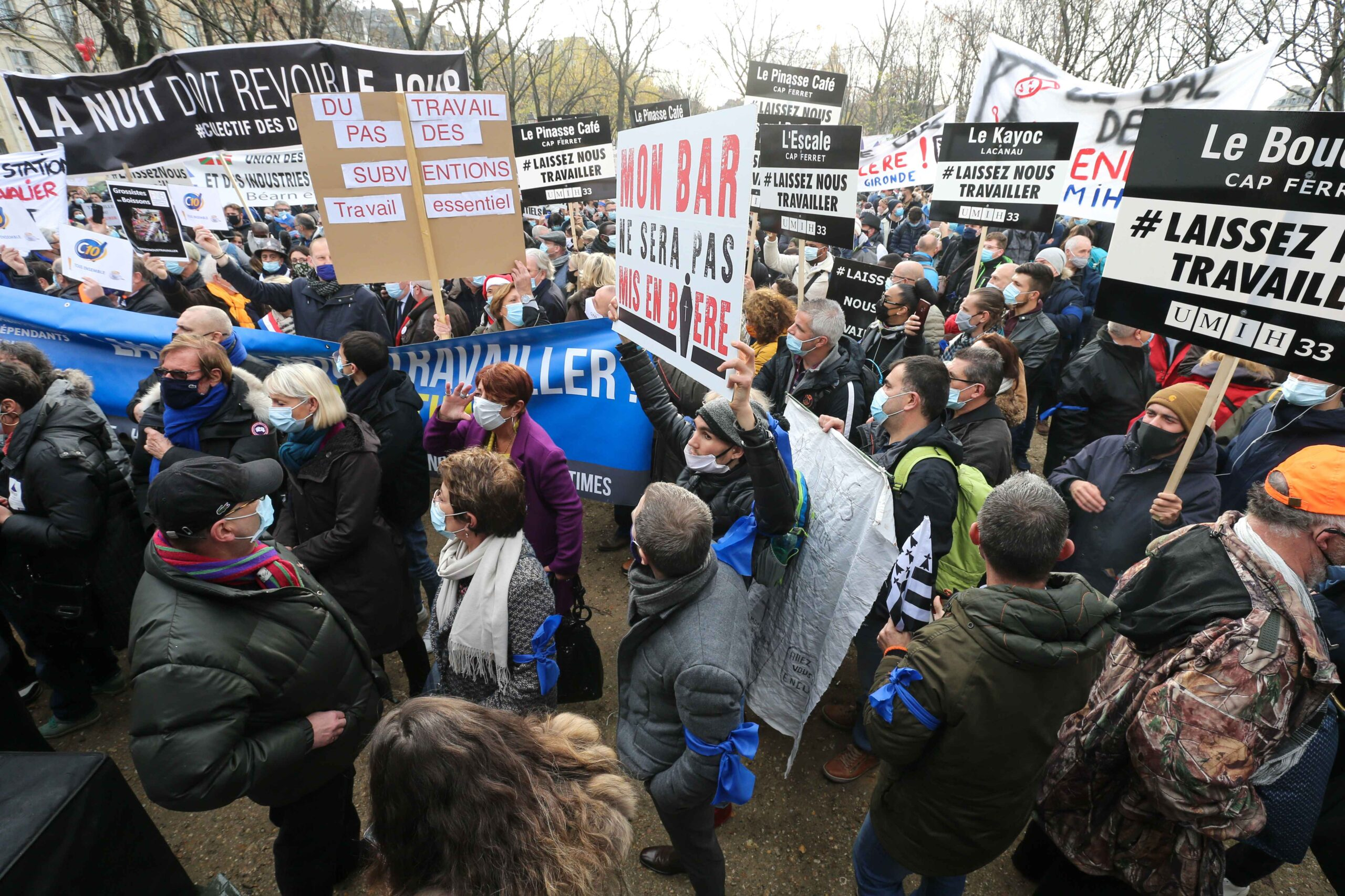 """Protesters hold placards and banners reading """"let us work"""" on December 14, 2020 in Paris during a demonstration of hotel and restaurant owners as well as tourism professionals to demand their businesses to reopen amidst the Covid-19 pandemic, caused by the"""