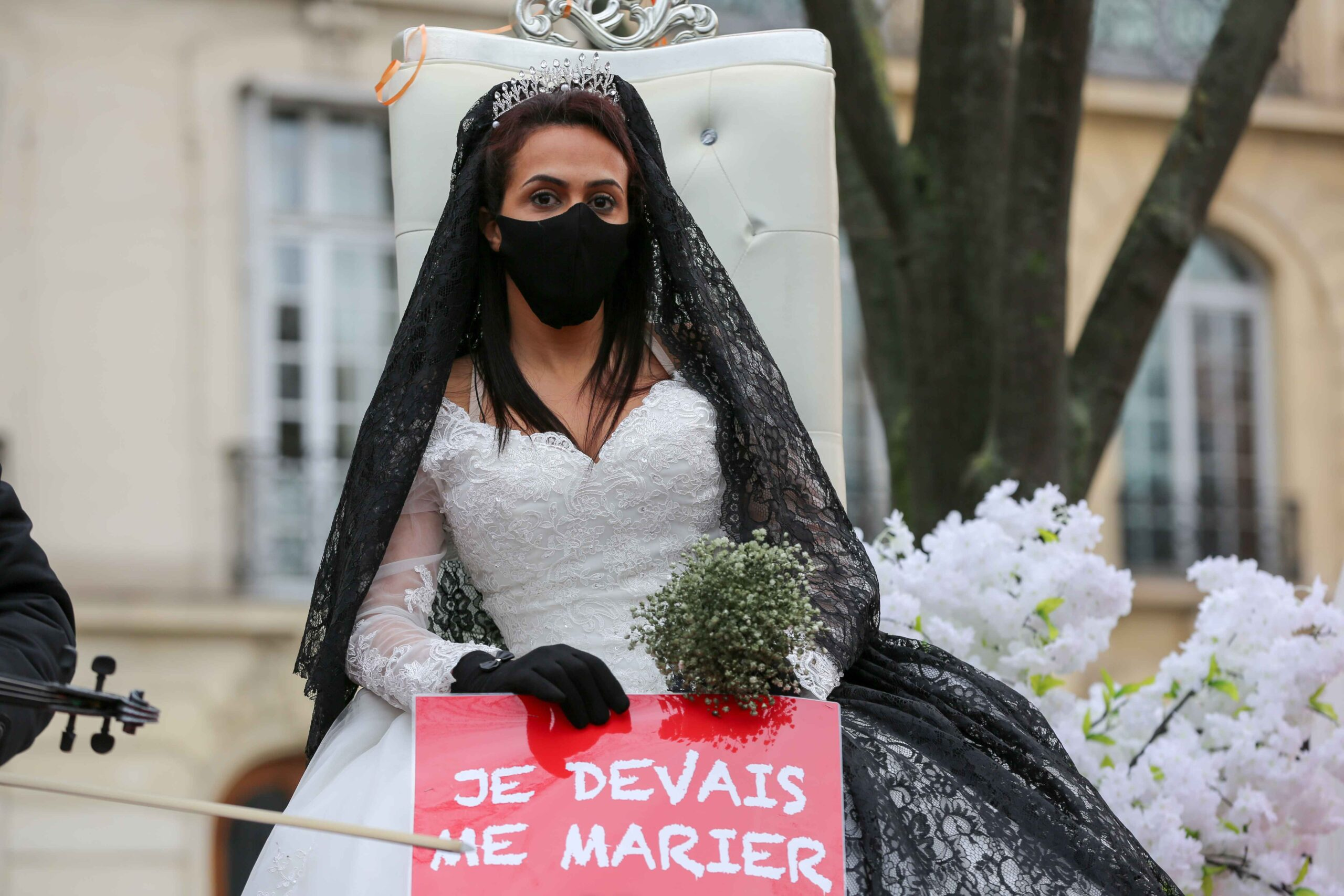 """Protesters play a scene with a a placard reading """"I was supposed to get married"""" on December 14, 2020 in Paris during a demonstration of hotel and restaurant owners as well as tourism professionals to demand their businesses to reopen amidst the Covid-19 p"""
