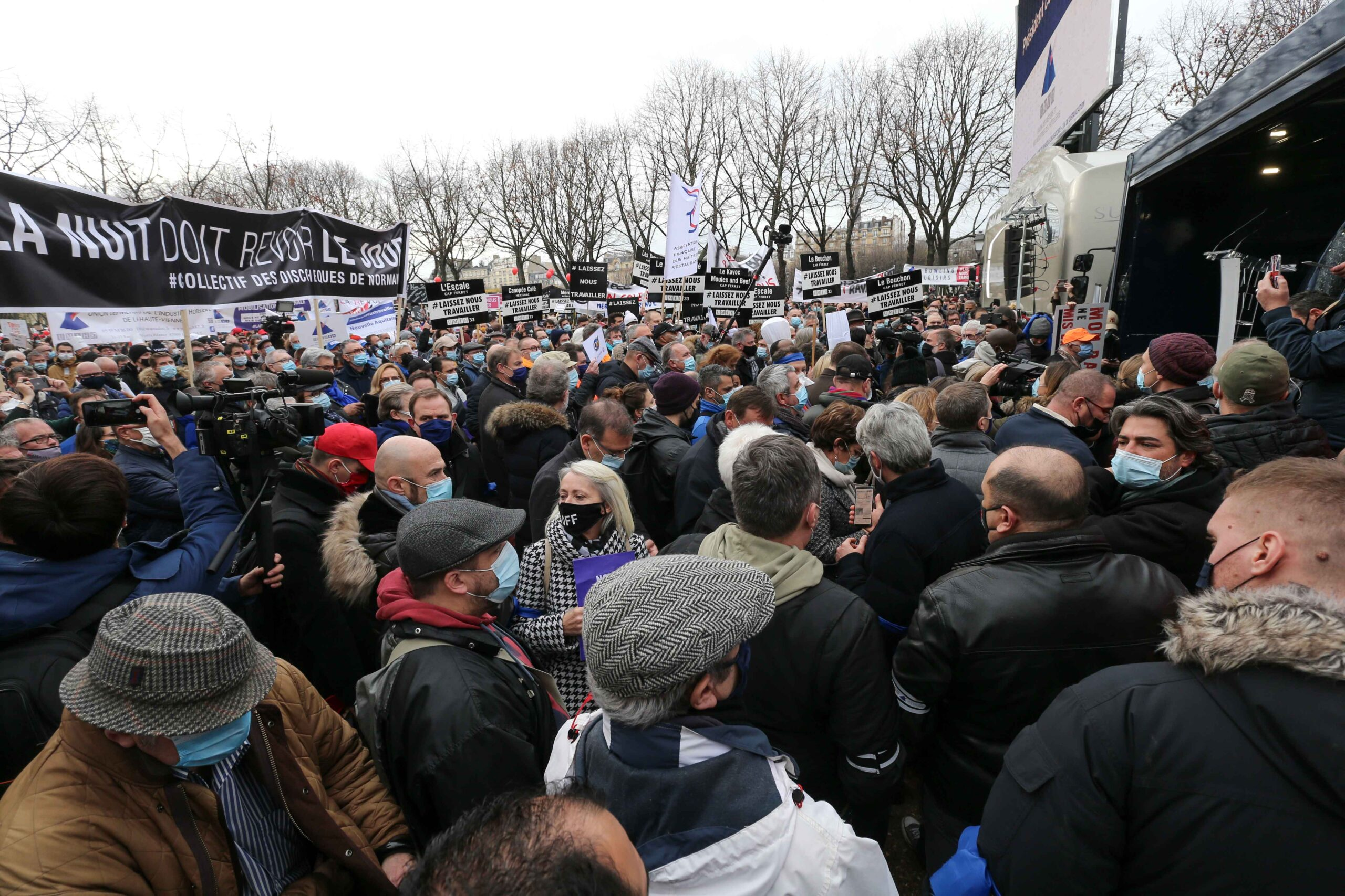 Protesters hold placards and banners on December 14, 2020 in Paris during a demonstration of hotel and restaurant owners as well as tourism professionals to demand their businesses to reopen amidst the Covid-19 pandemic, caused by the novel coronavirus.