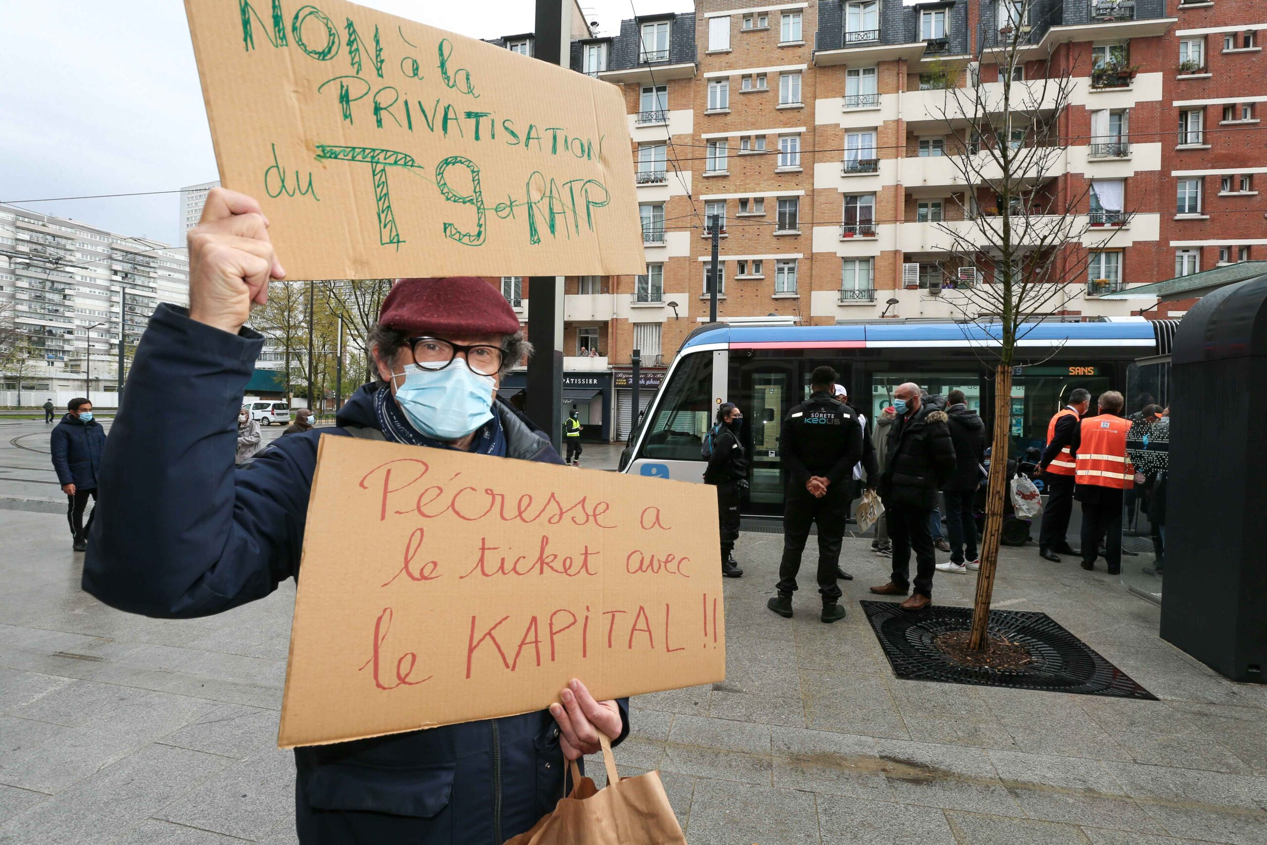 An opponent holds a placard reading « No to privatization of T9 and RATP » and « Pecresse is popular with capital » as he demonstrates on the opening day of the new tramway T9 tram line between Porte de Choisy and Orly City, southeastern Paris, on Apr