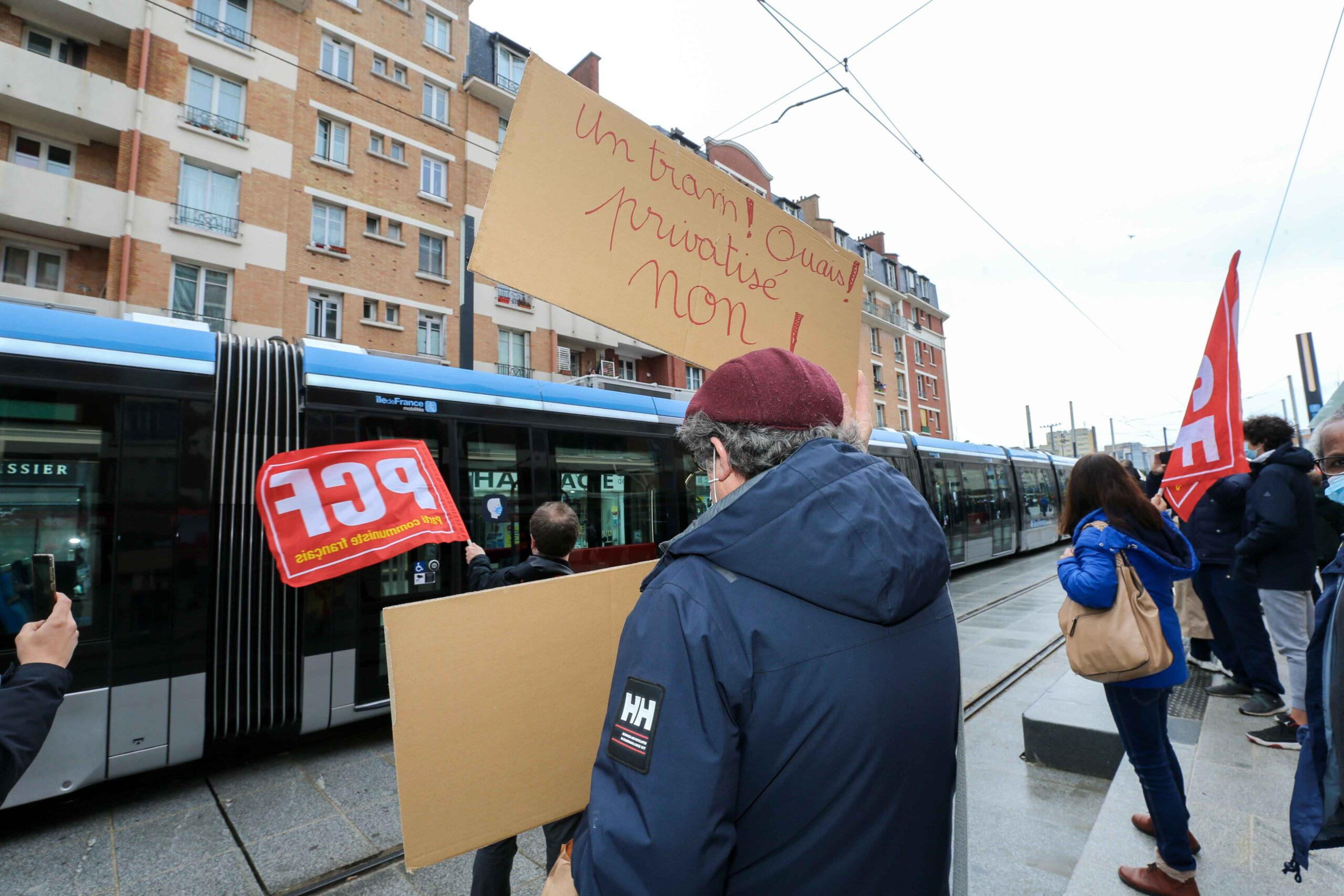 Opponents holding flags an placard  demonstrate during the opening day of the new tramway T9 tram line between Porte de Choisy and Orly City, southeastern Paris, on April 10, 2021 at Porte de Choisy, in Paris.Line T9 connects Porte de Choisy Paris Métro