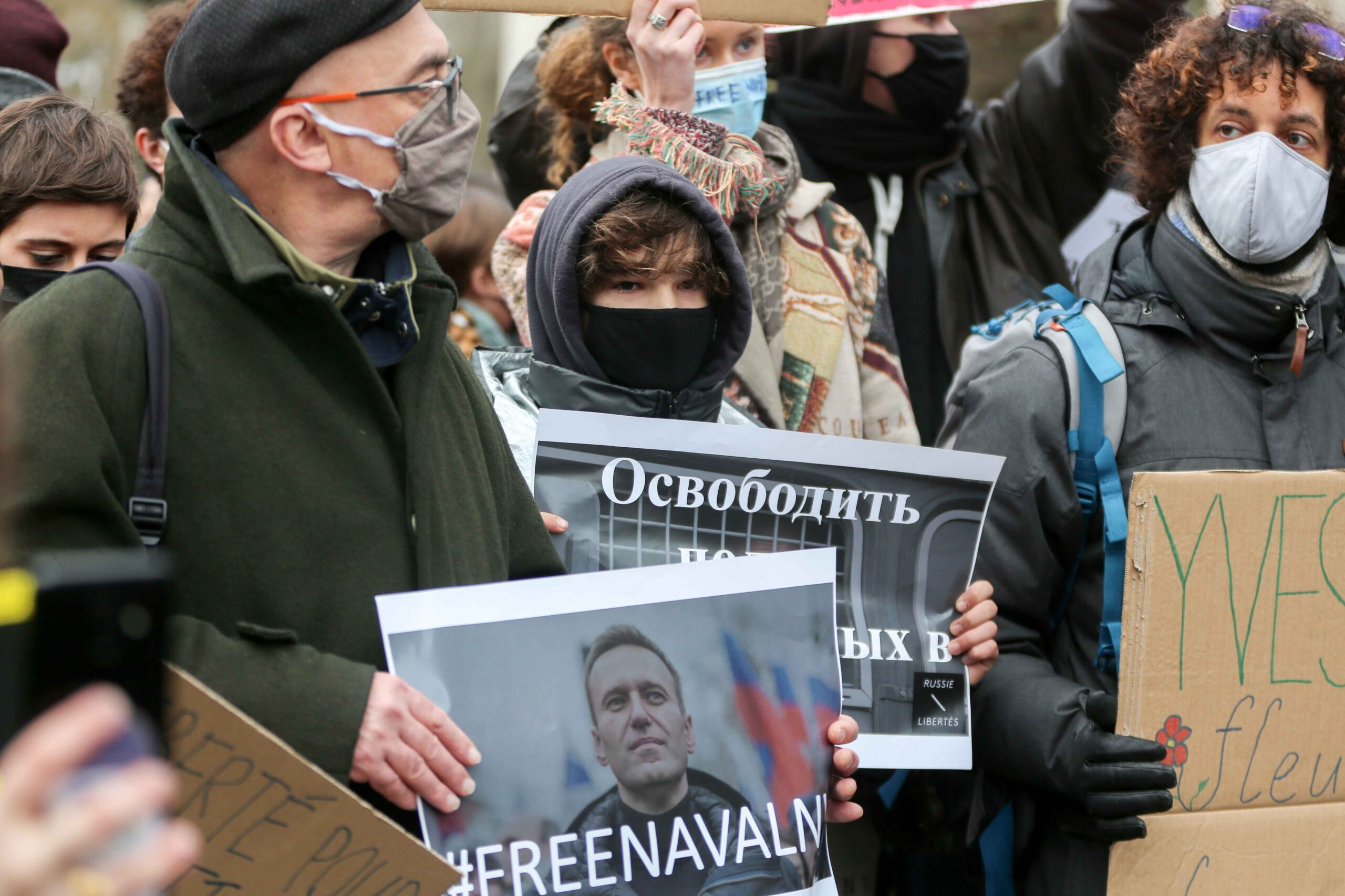 Protesters hold placards during a rally in support of jailed opposition leader Alexei Navalny in place du Trocadéro, in Paris on January 23, 2021. Navalny, 44, was detained last Sunday upon returning to Moscow after five months in Germany recovering from
