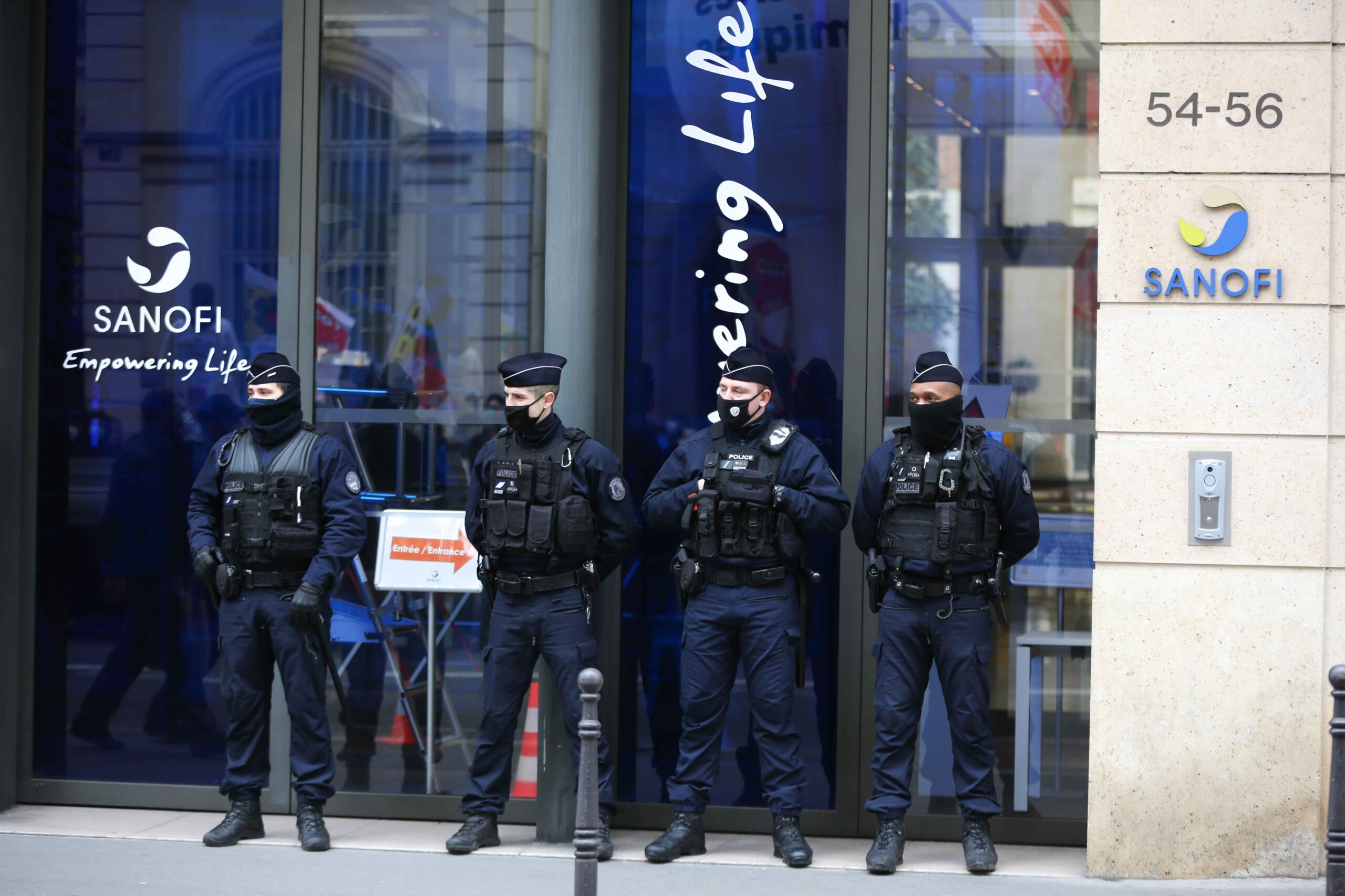 Police officers  protect access to the the French pharma giant Sanofi group headquarters in Paris, on February 4, 202, during a day of action to highlight the current economic and cultural difficulties being experienced across France as the coronavirus (Co