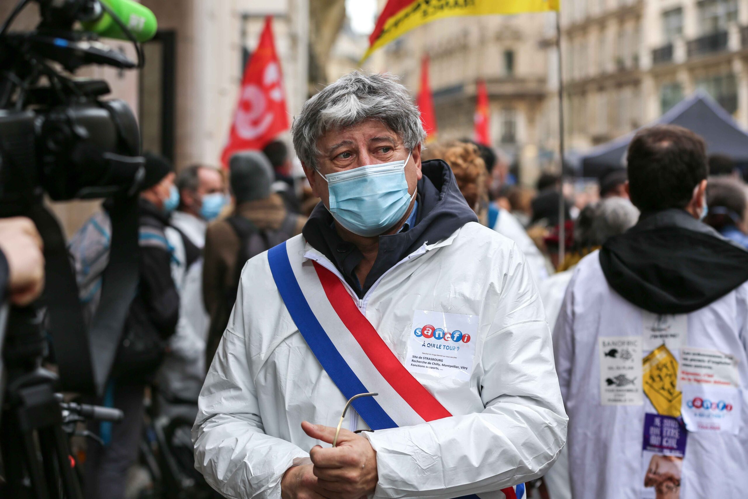 Member of parliament of French leftist La France Insoumise (LFI) party Eric Coquerel (C), wearing a lab coat, talks to the press during a gathering in front of the French pharma giant Sanofi group headquarters in Paris, on February 4, 202, during a day of