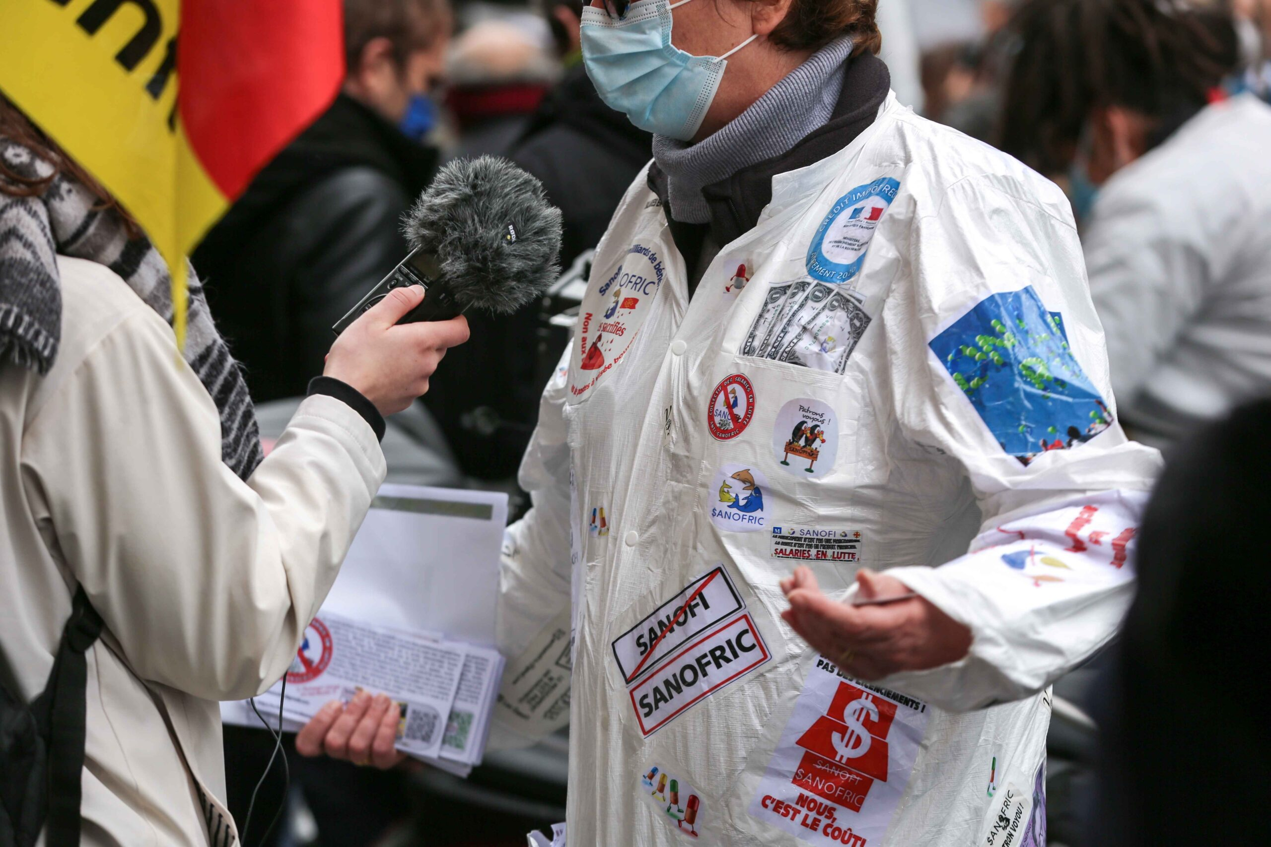 A demonstrator, wearing a lab coat, talks to the press during a gathering in front of the French pharma giant Sanofi group headquarters in Paris, on February 4, 202, during a day of action to highlight the current economic and cultural difficulties being e