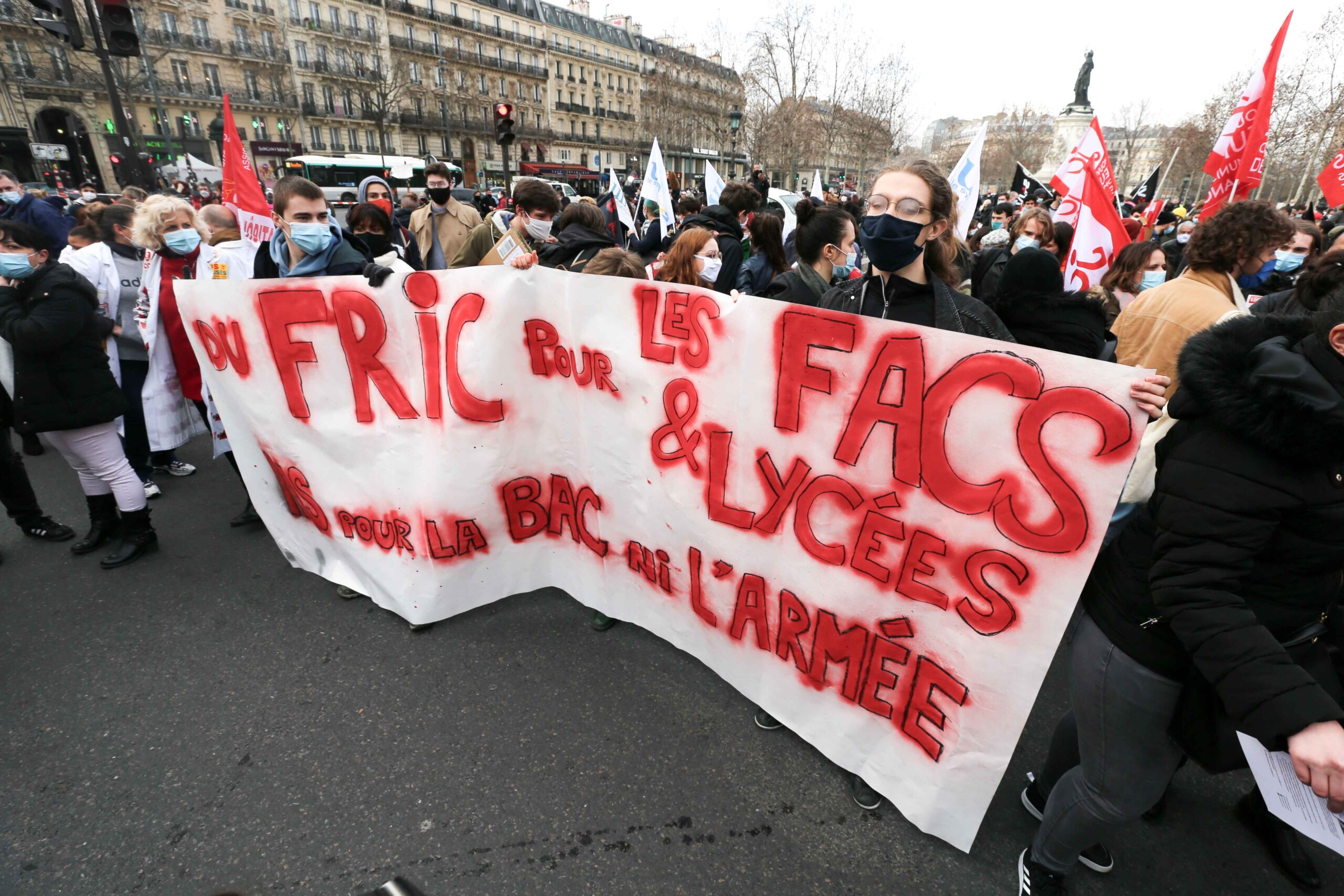 French students demonstrate behind a banner on Place de la Liberté on February 4, 2021, in Paris, during a day of action to highlight the current economic and cultural difficulties being experienced across France as the coronavirus (Covid-19) pandemic con