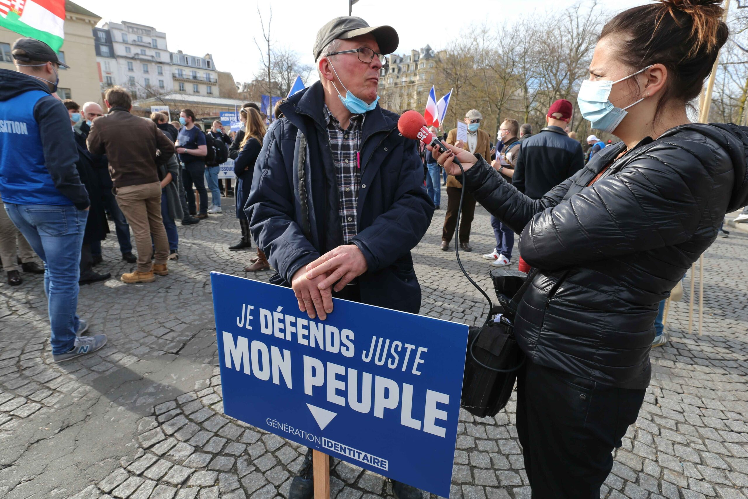 A member of far right group Generation Identitaire (GI) holds a placard reading « I'm just defending my people » speaks with the press during a protest against its potential dissolution in Place Denfert Rochereau, in Paris on February 20, 2021. The dis