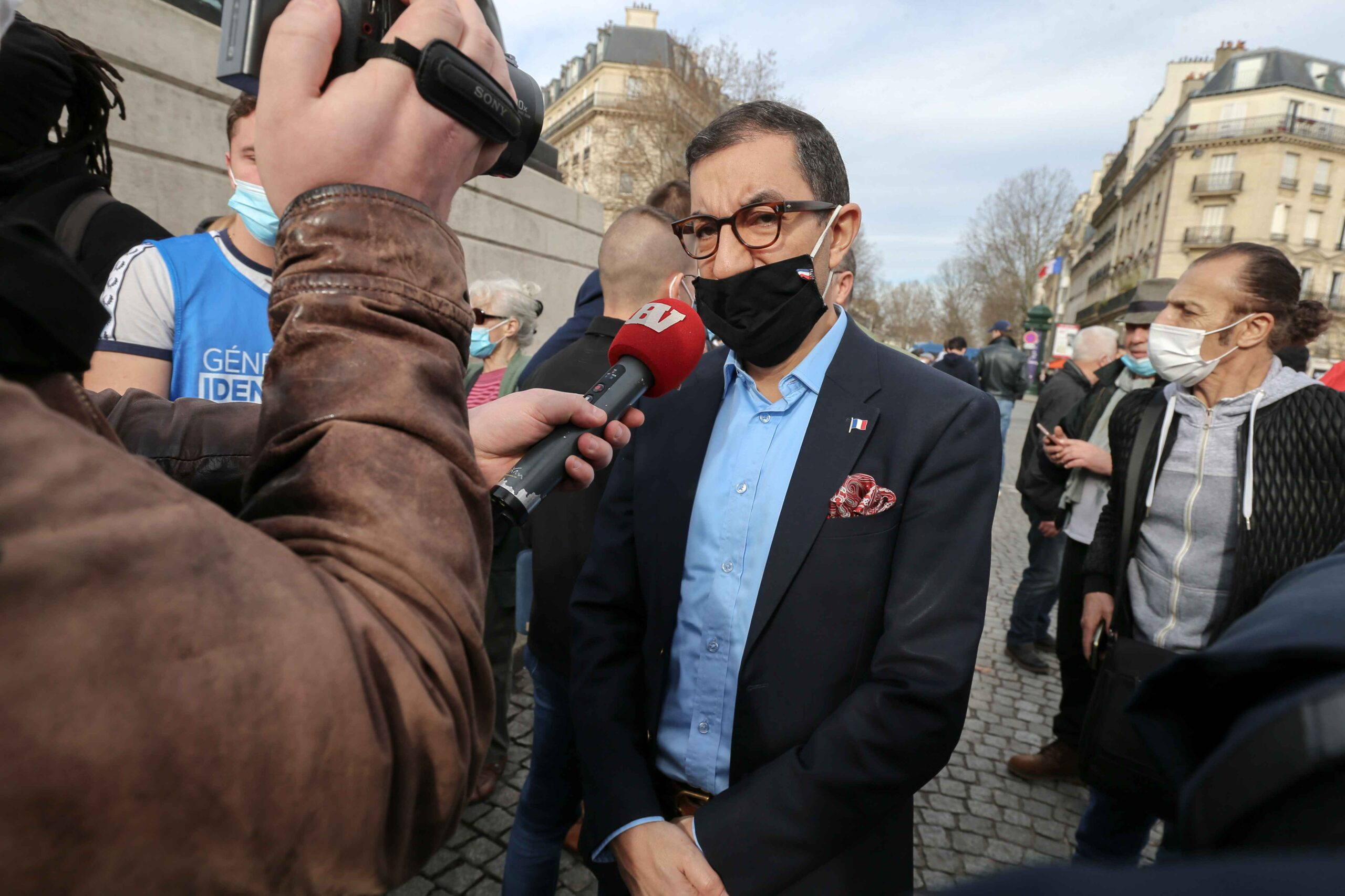 Member of far-right Rassemblement National's (RN) Jean Messiha (C) speaks with the press during a protest against the far right Generation Identitaire group's potential dissolution in Place Denfert Rochereau, in Paris on February 20, 2021. The dissolution