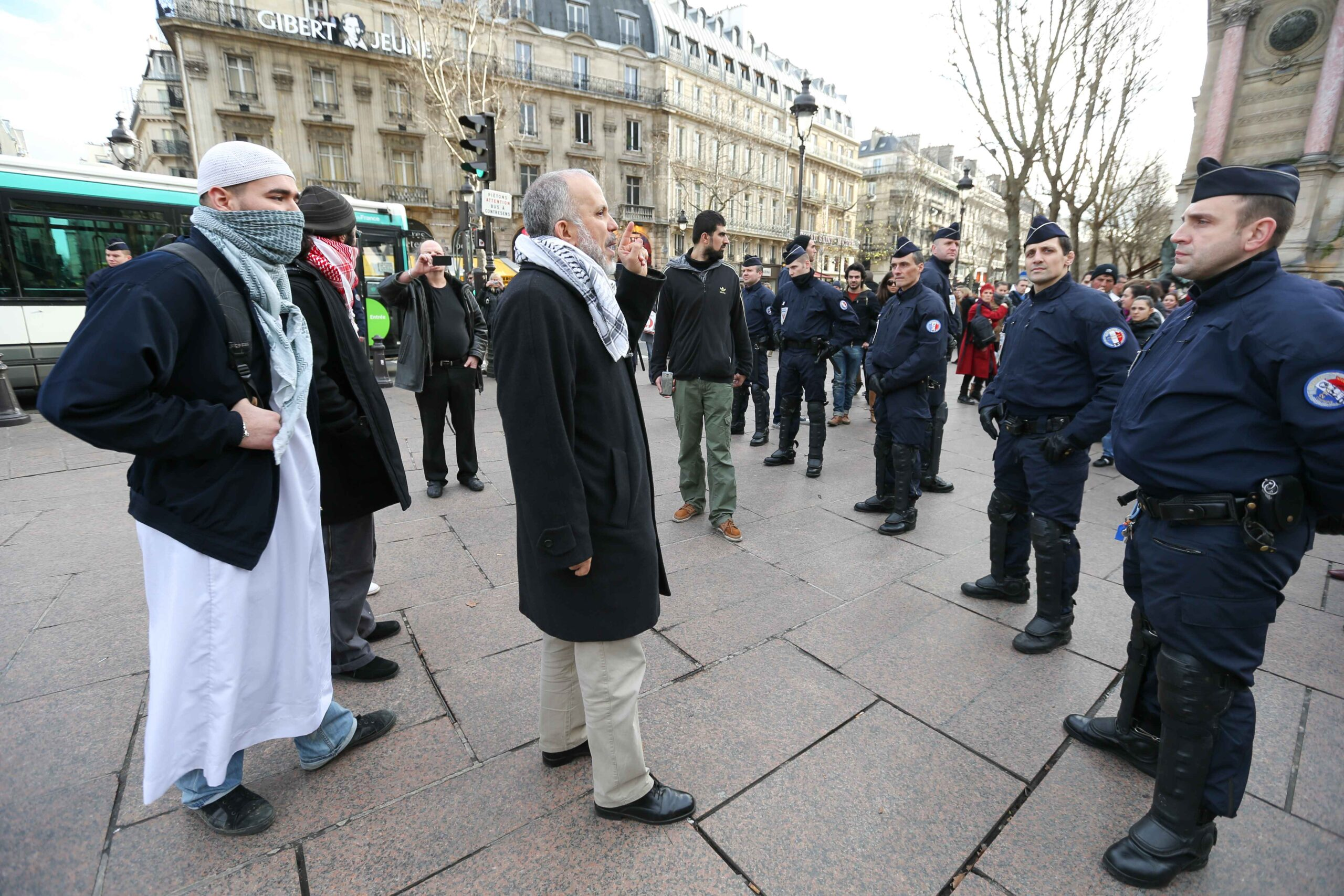 This picture taken on December 29, 2012, in Paris, shows the President of the Cheikh Yassine collective Abdelhakim Sefrioui (C with a white djellaba) protesting in front of French anti-riot gendarmes to support Palestine.Abdelhakim Sefrioui is involved in