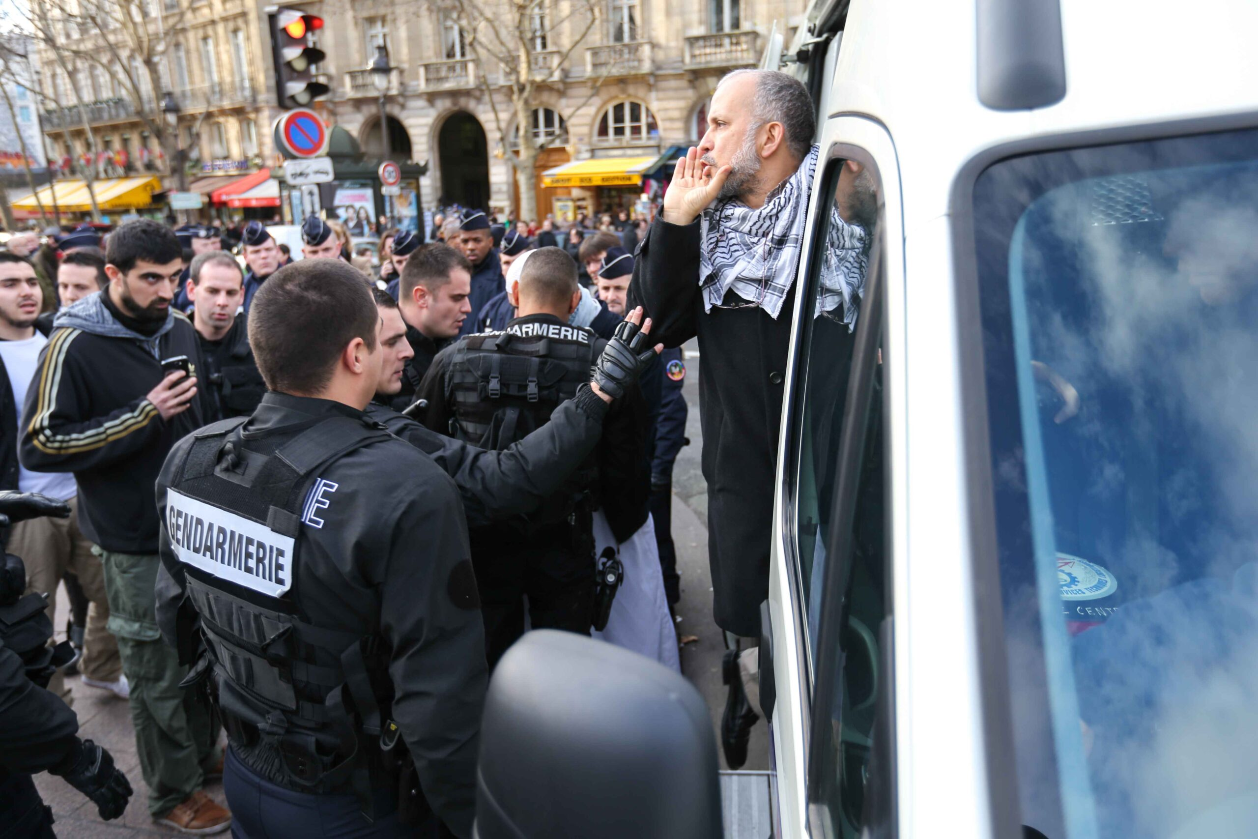 This picture taken on December 29, 2012, in Paris, shows the President of the Cheikh Yassine collective Abdelhakim Sefrioui (C with a white djellaba) being arrested by French anti-riot gendarmes after a protest to support Palestine.Abdelhakim Sefrioui is